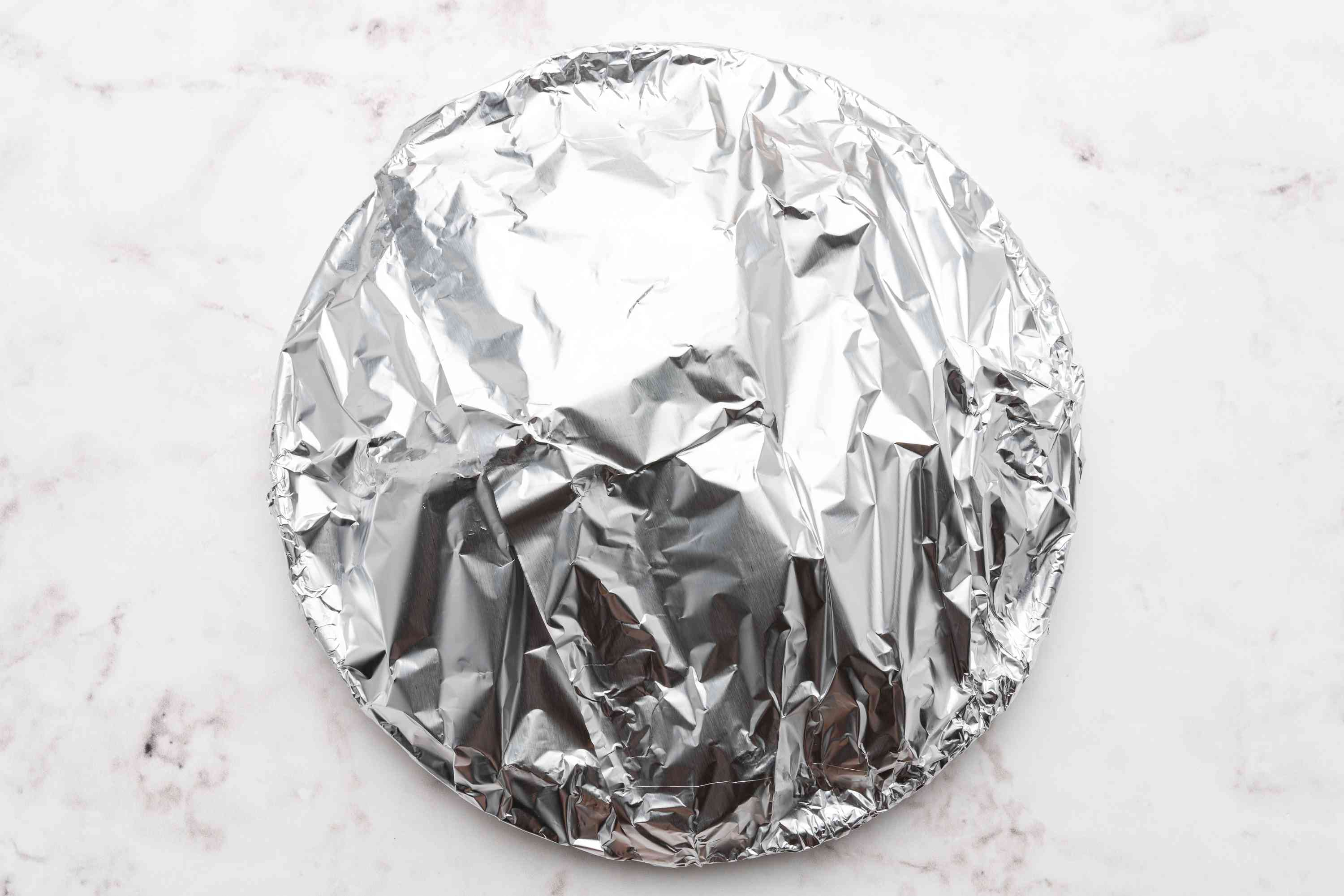 pork cutlets on a plate covered with aluminum foil