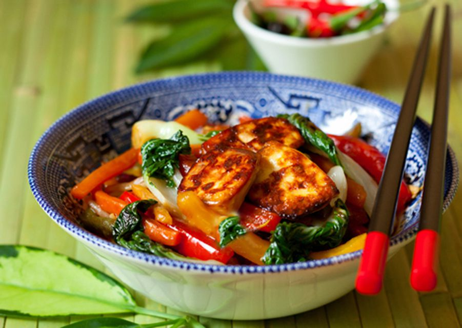 Thai vegetable stir-fry with fried tofu in a bowl along with chopsticks