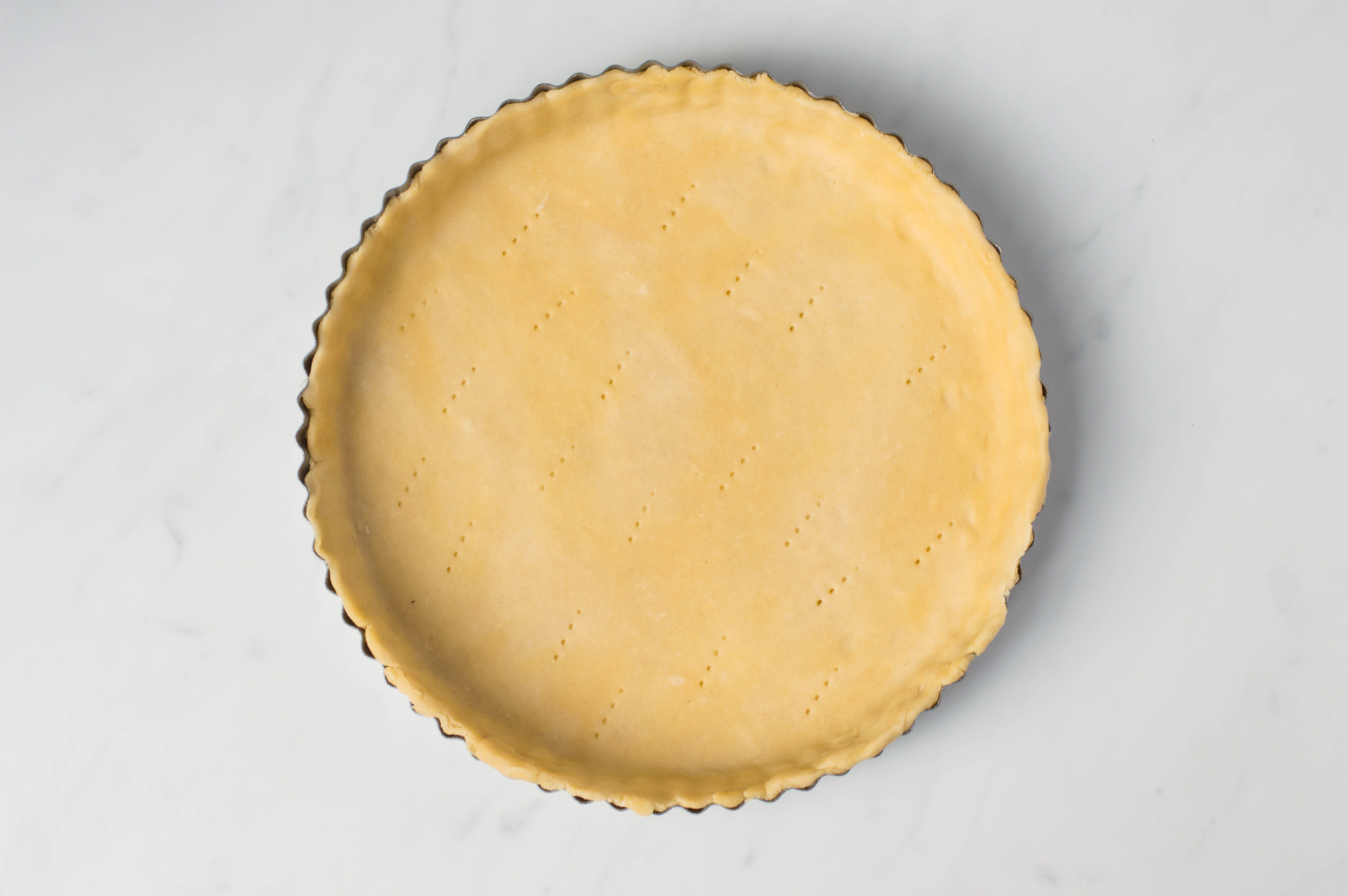 Dough in tart pan with holes pricked in base