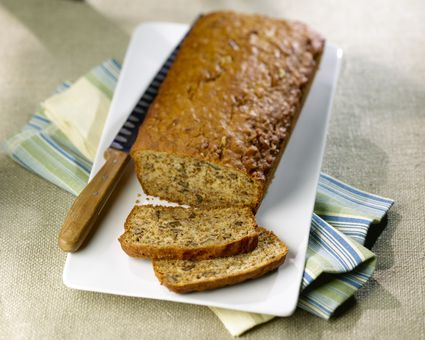 Banana Bread partially sliced on a white plate with a knife