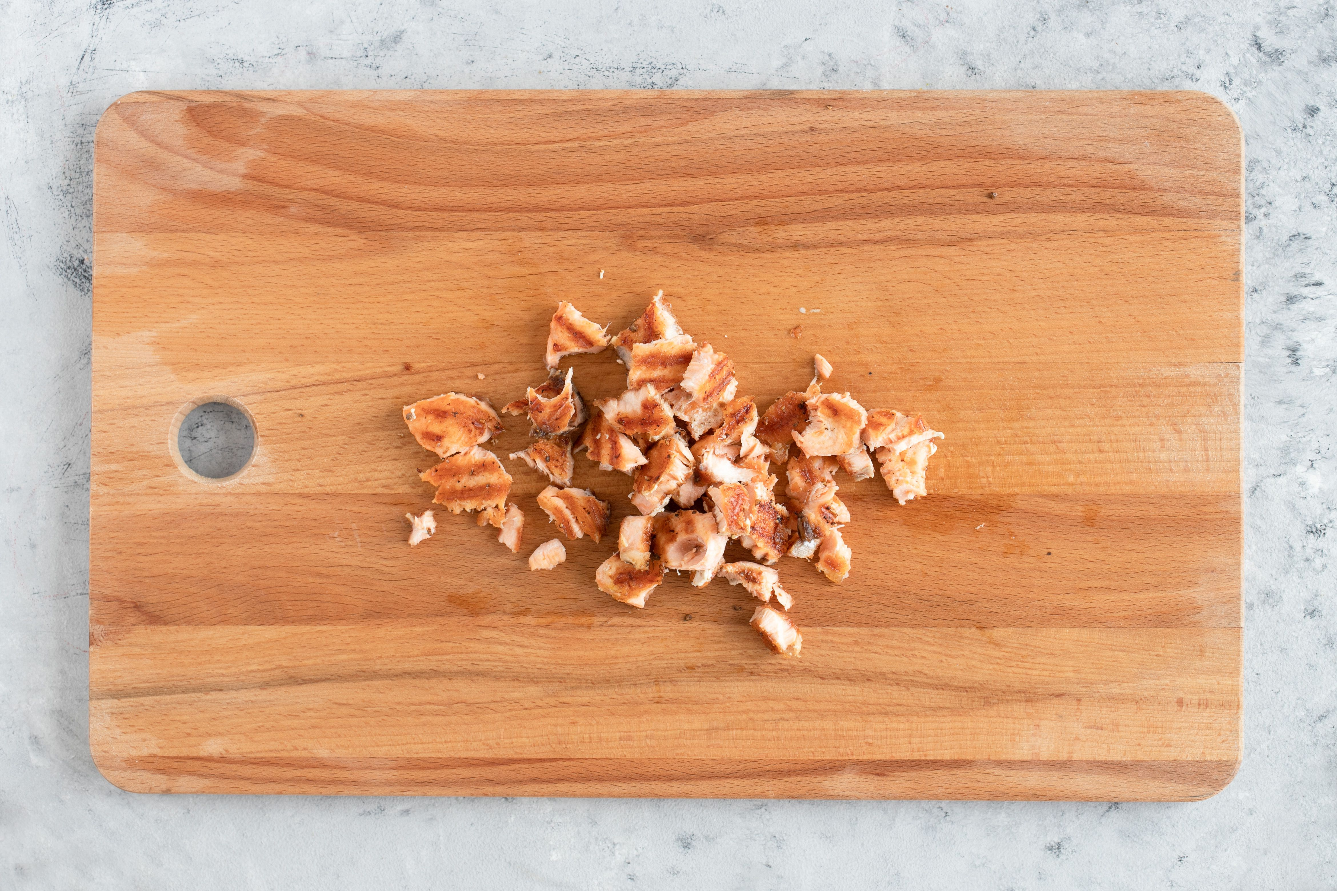 Salmon broken into large pieces on cutting board