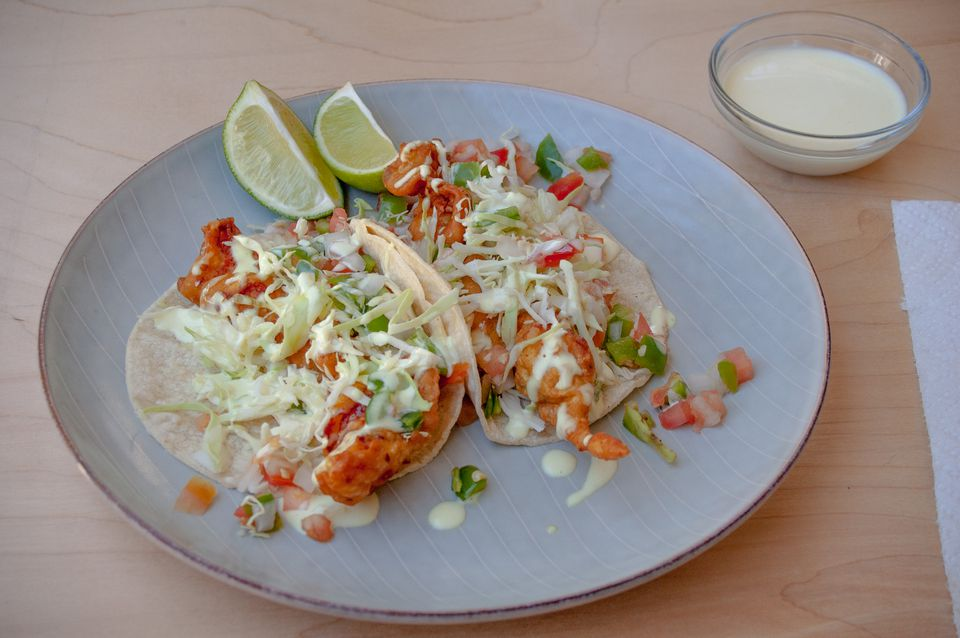 Battered and fried fish tacos with pico de gallo, sauce and limes