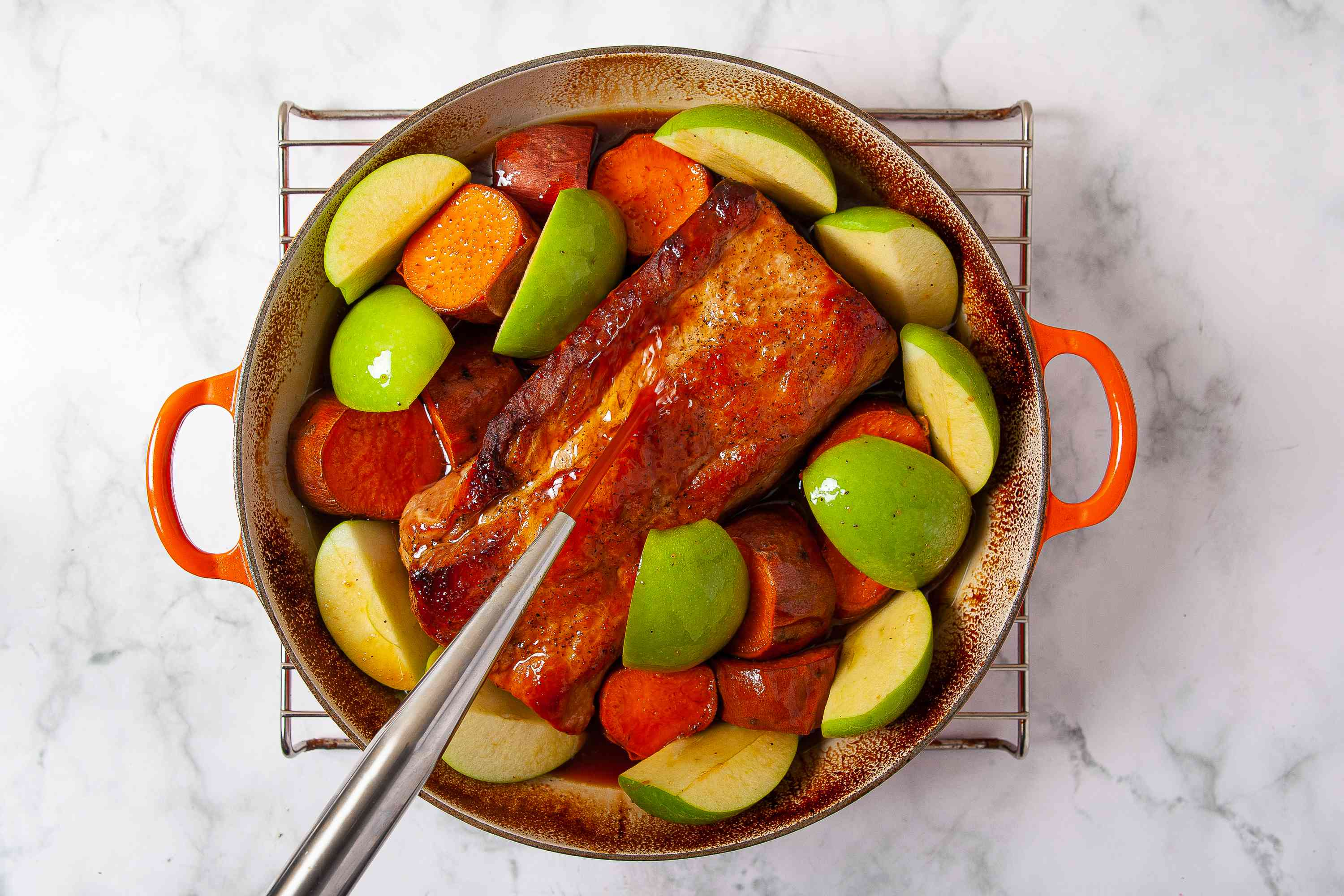 basting pork loin while it's cooking in a Dutch oven with apples and sweet potatoes