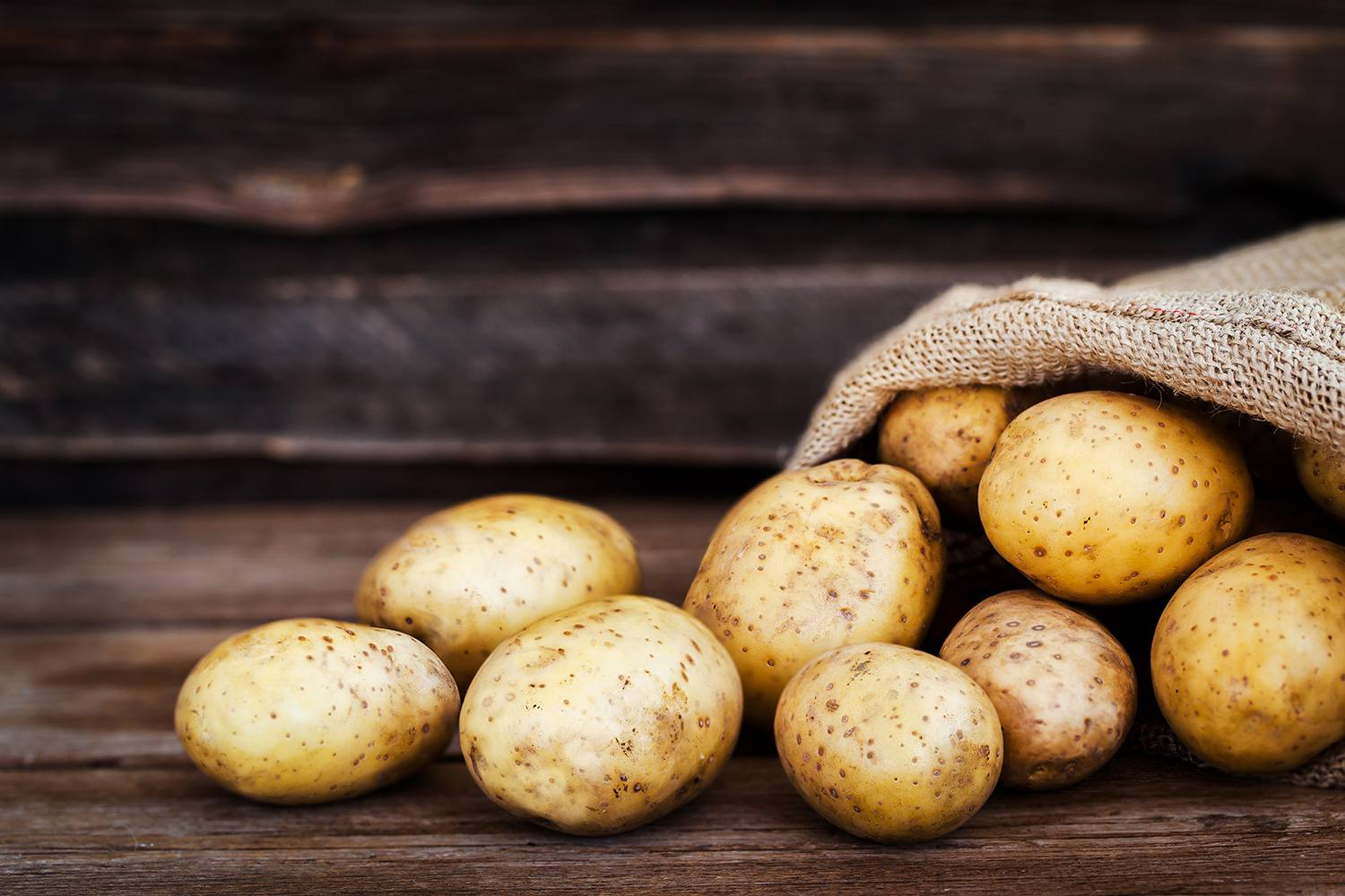 Raw fresh potatoes in the sack on wooden background