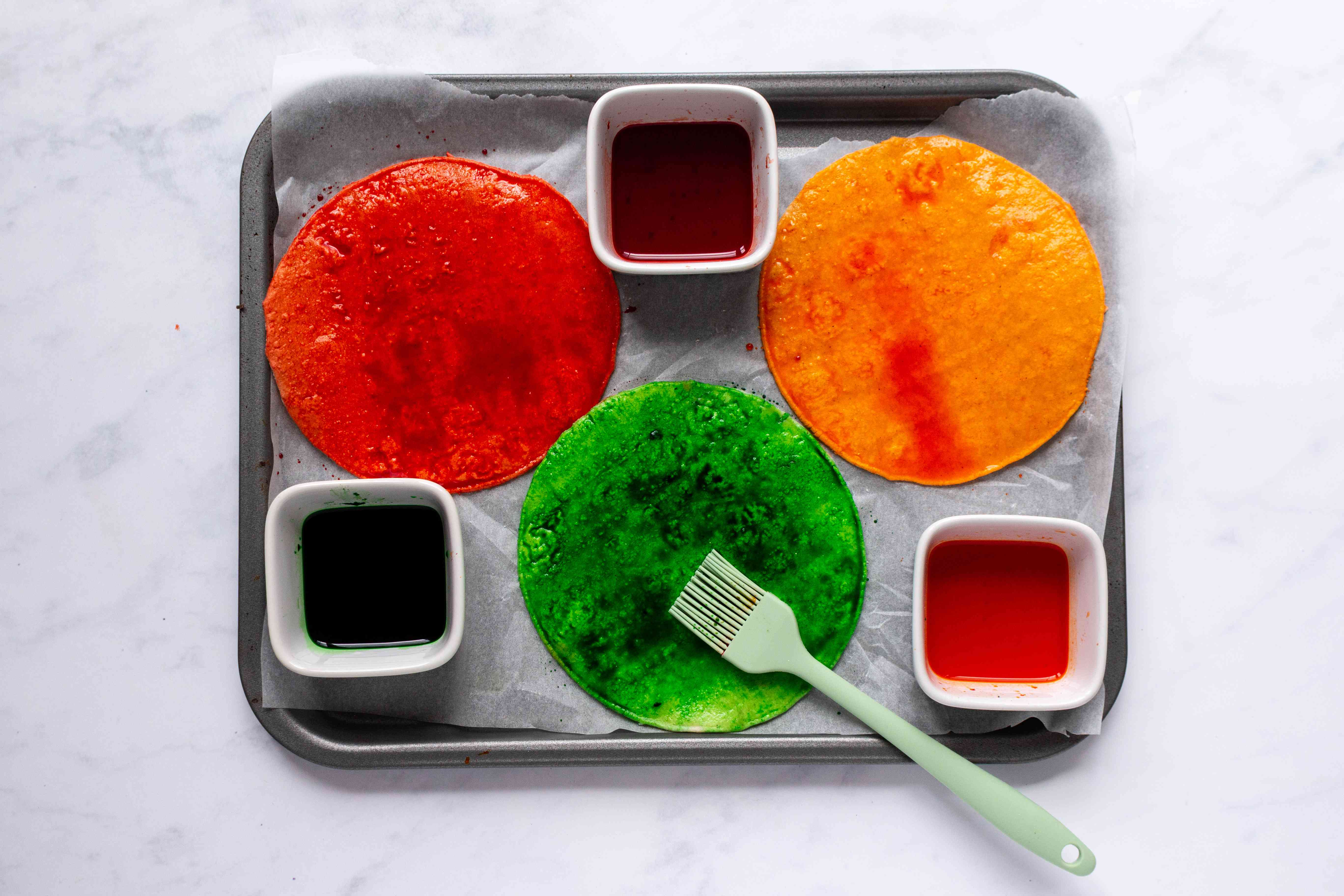 brush tortillas with food coloring on a baking sheet