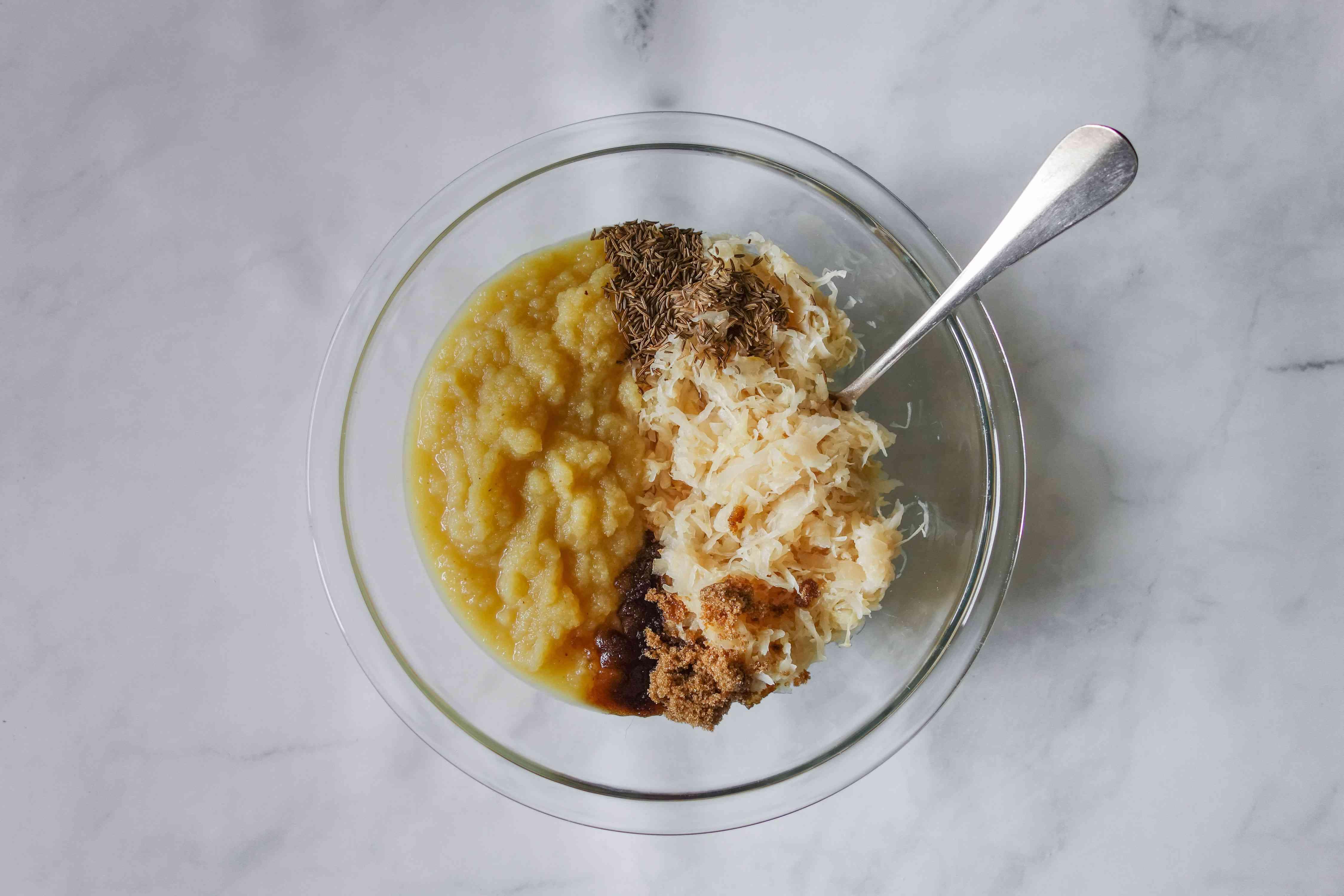 Mixing sauerkraut, applesauce, brown sugar, and caraway seeds in a bowl