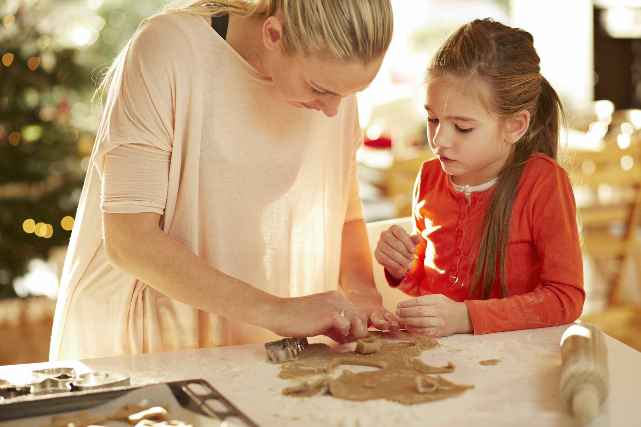 Mother helping daughter with christmas cookies