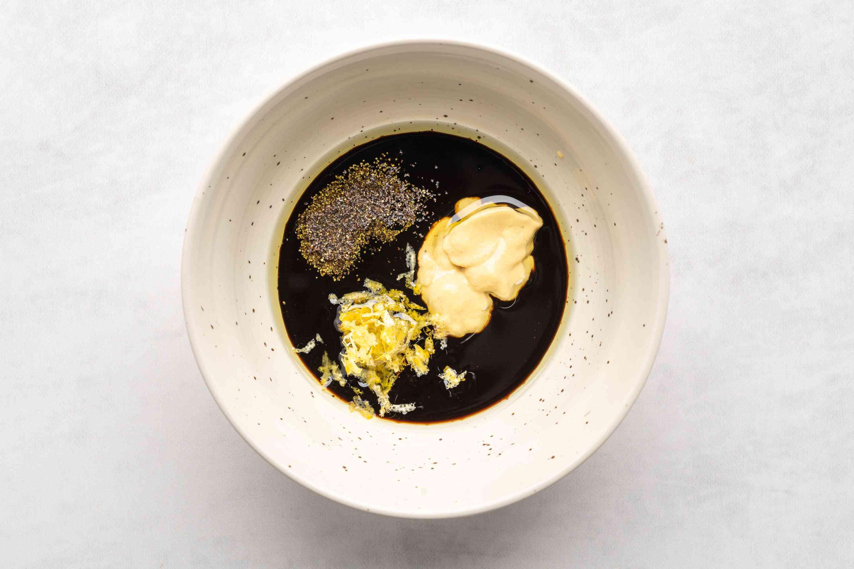 balsamic vinegar, olive oil, mustard, lemon zest, and black pepper in a bowl