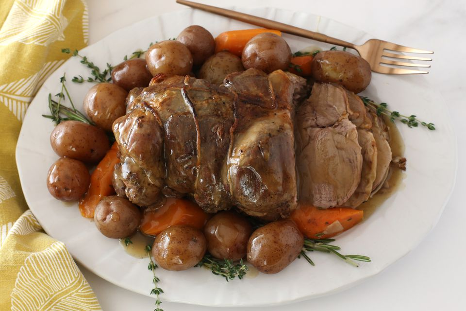 Instant Pot leg of lamb on a platter with vegetables and herbs.