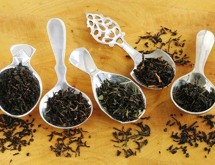 Assorted black tea leaves on tea spoons