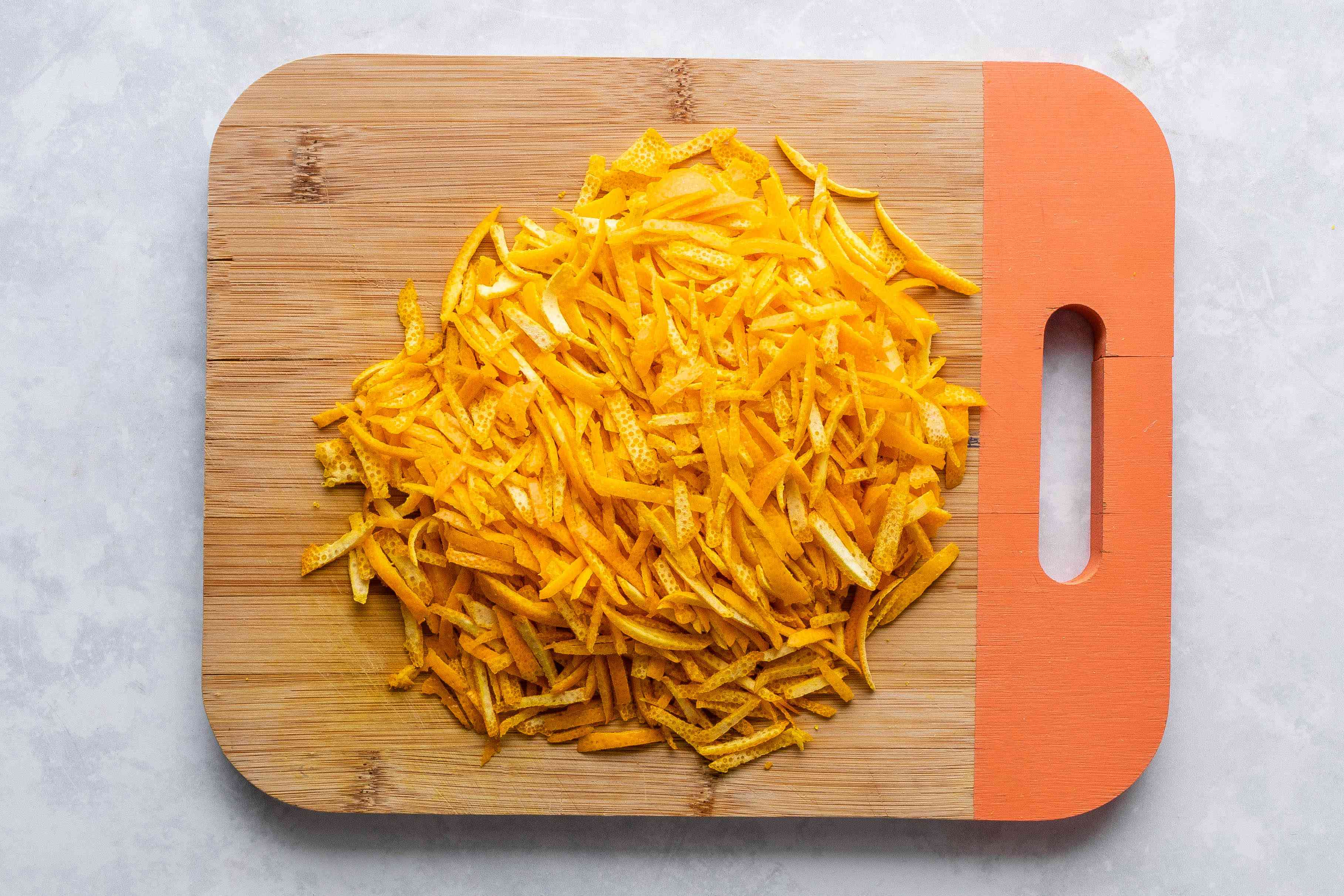 orange zest chopped into ribbon-like strips, on a wood cutting board