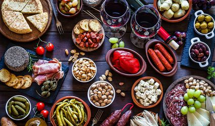 settings Tapas and wine on rustic wooden table shot from above