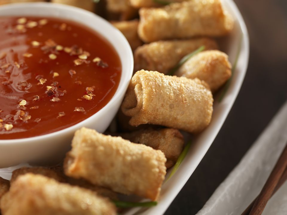 A plate of miniature egg rolls with plum sauce