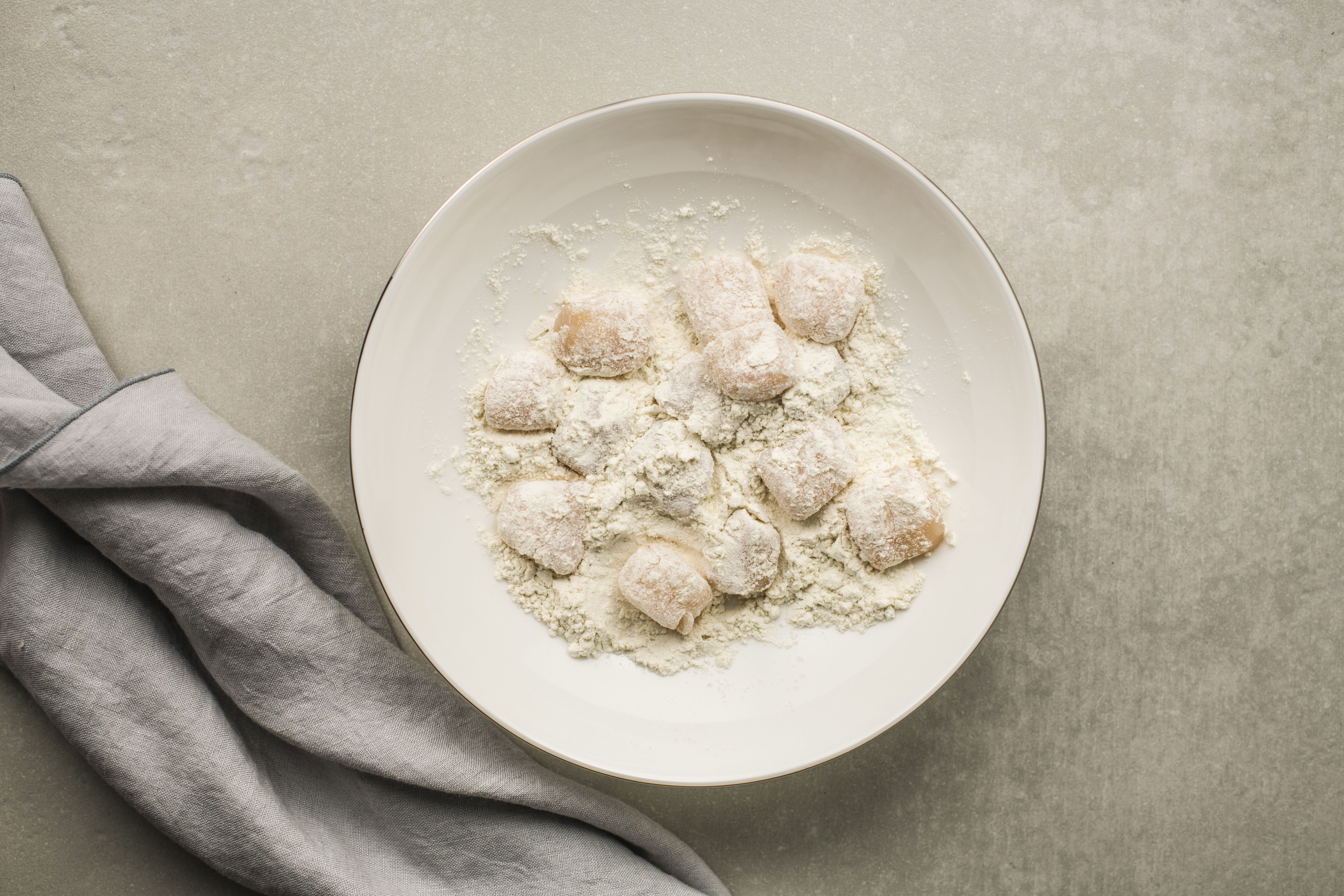 Scallops coated with flour in a bowl