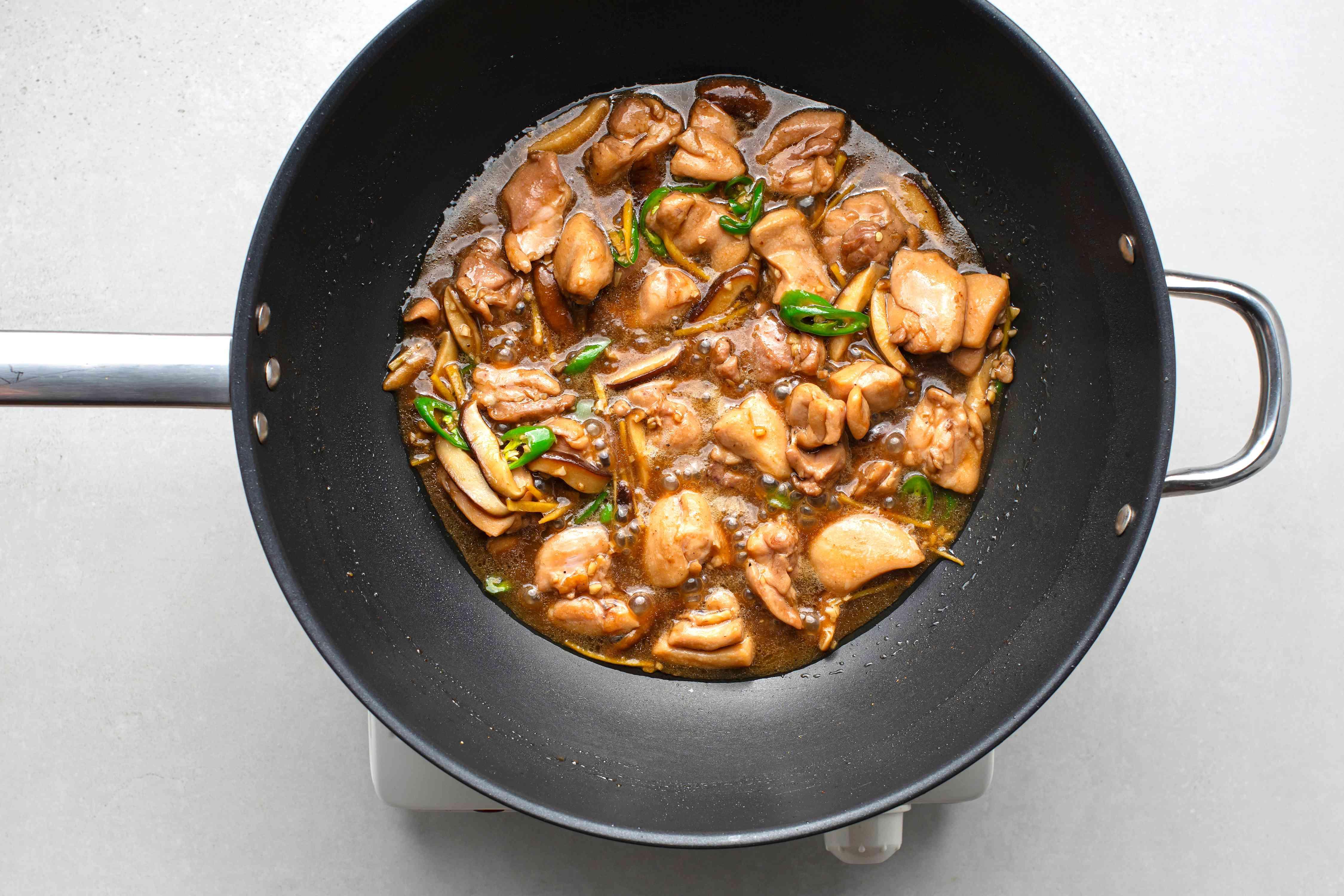 Thai tamarind chicken stir-fry cooking in a wok