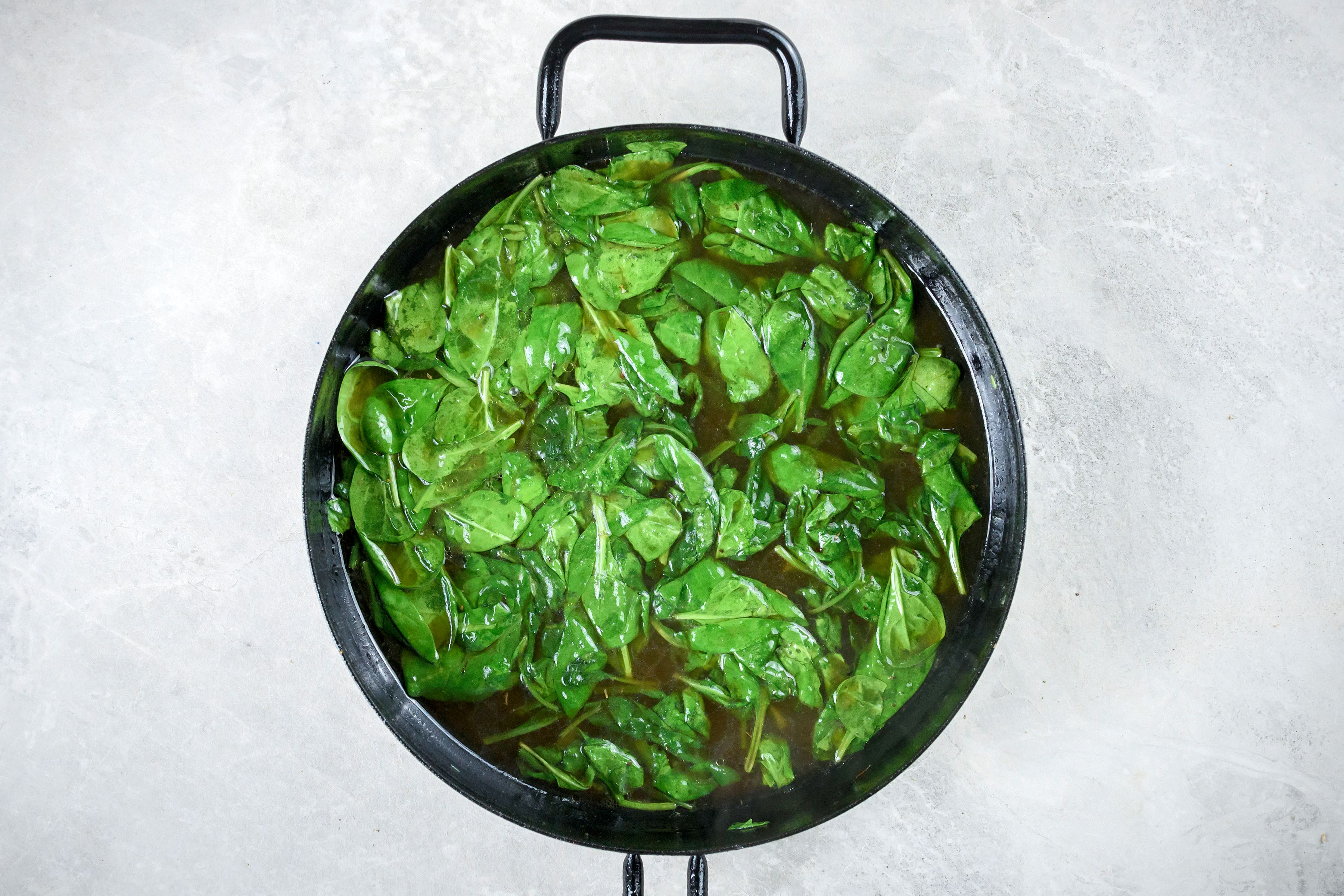 Greens steamed in chicken broth in cast-iron pan