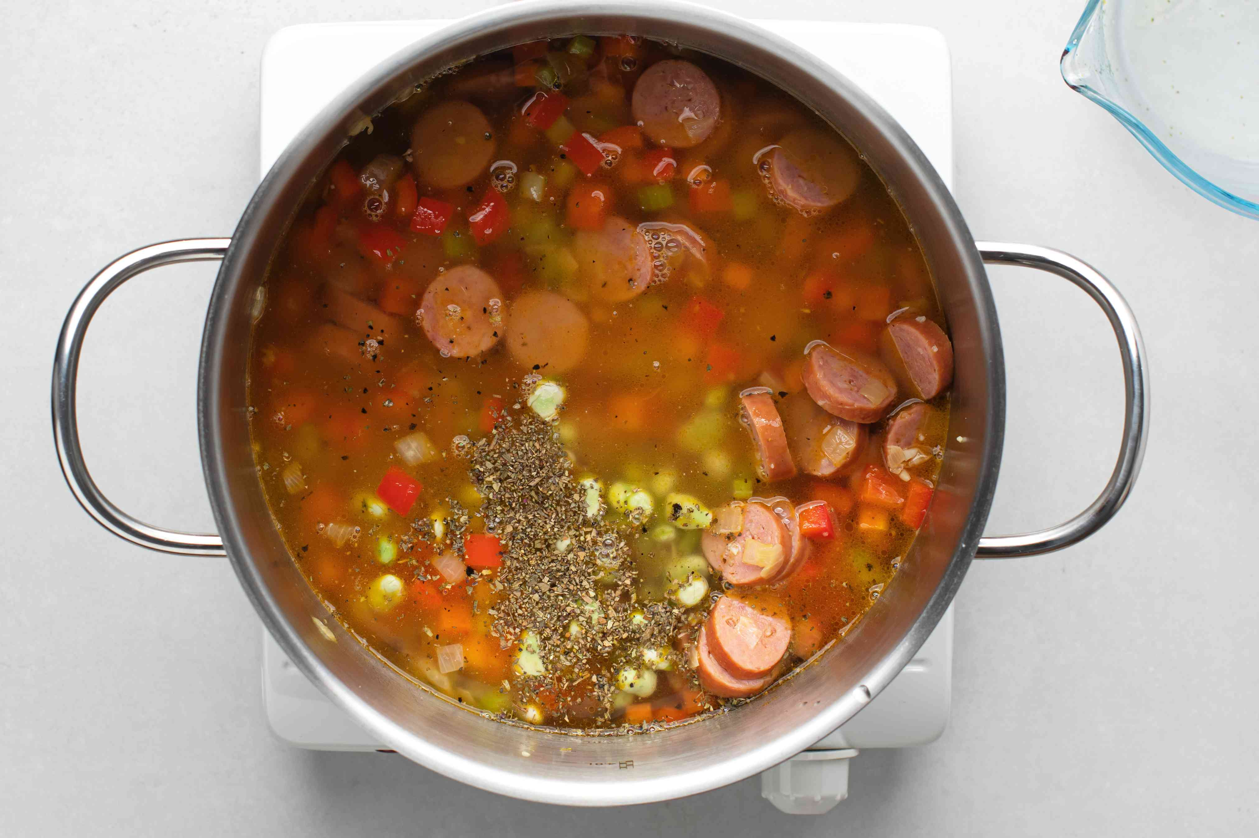 Add the lima beans, salt, pepper, basil, and chicken stock to the sausage and vegetables in the pot