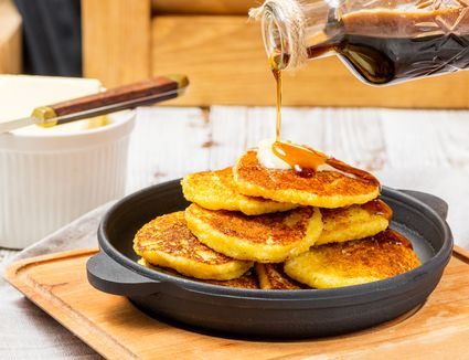 Cornmeal johnnycakes in a skillet with maple syrup
