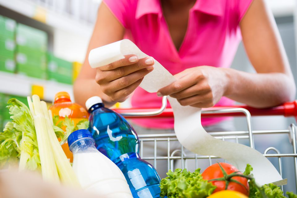 woman holding receipt while pushing grocery cart