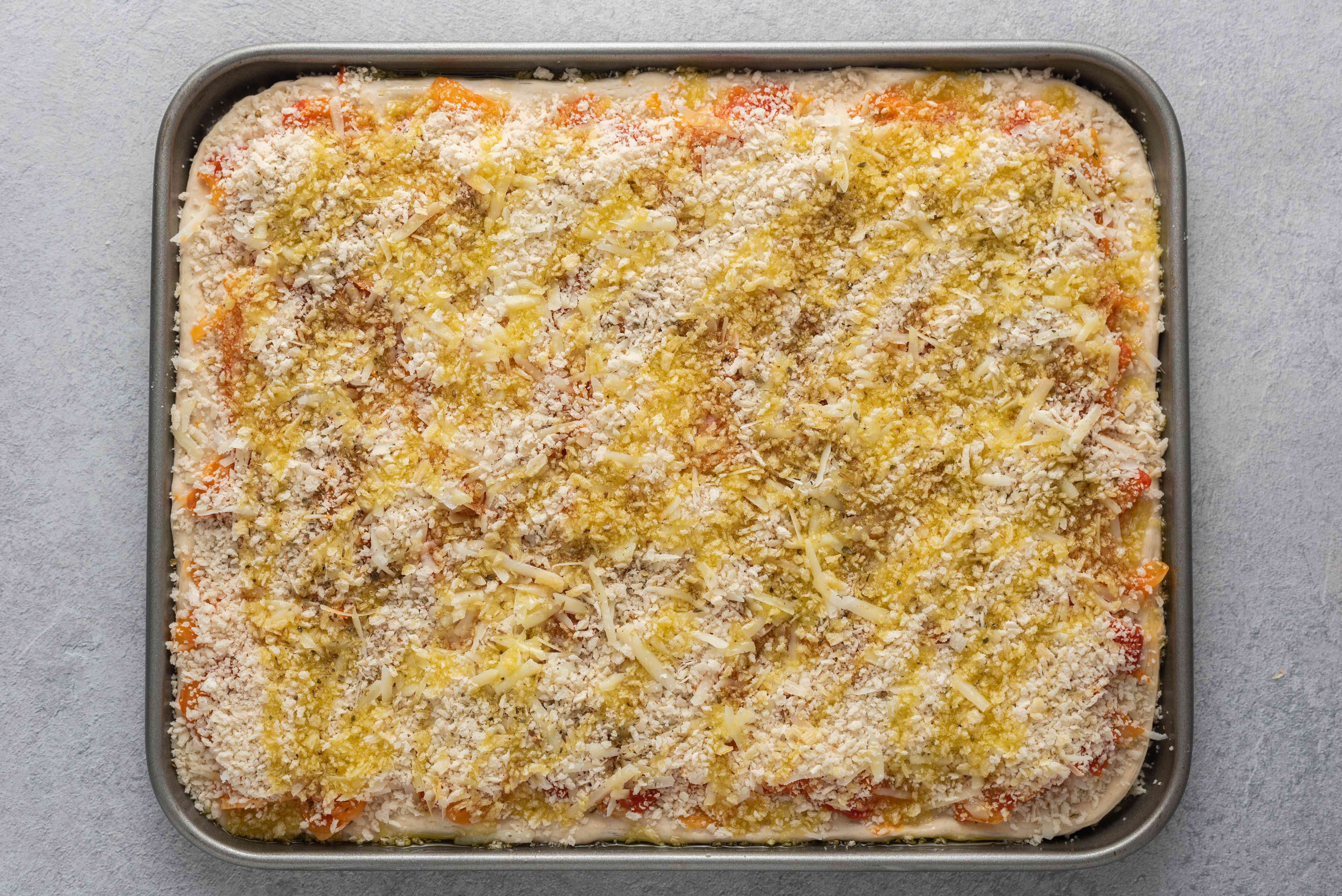 grated cheese, breadcrumbs, oregano and olive oil on top of pizza