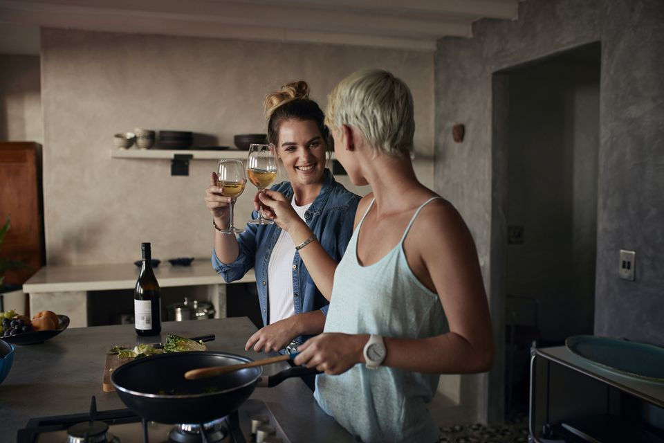 Two young women cooking together in loft apartment, toasting in wine
