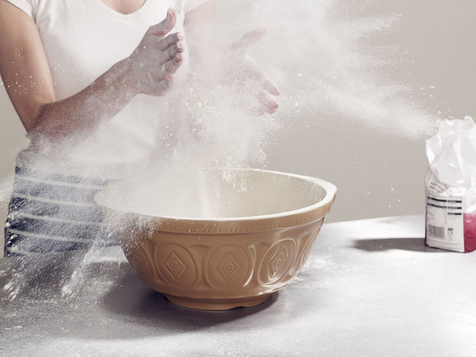 Woman's hands covered in flour while baking