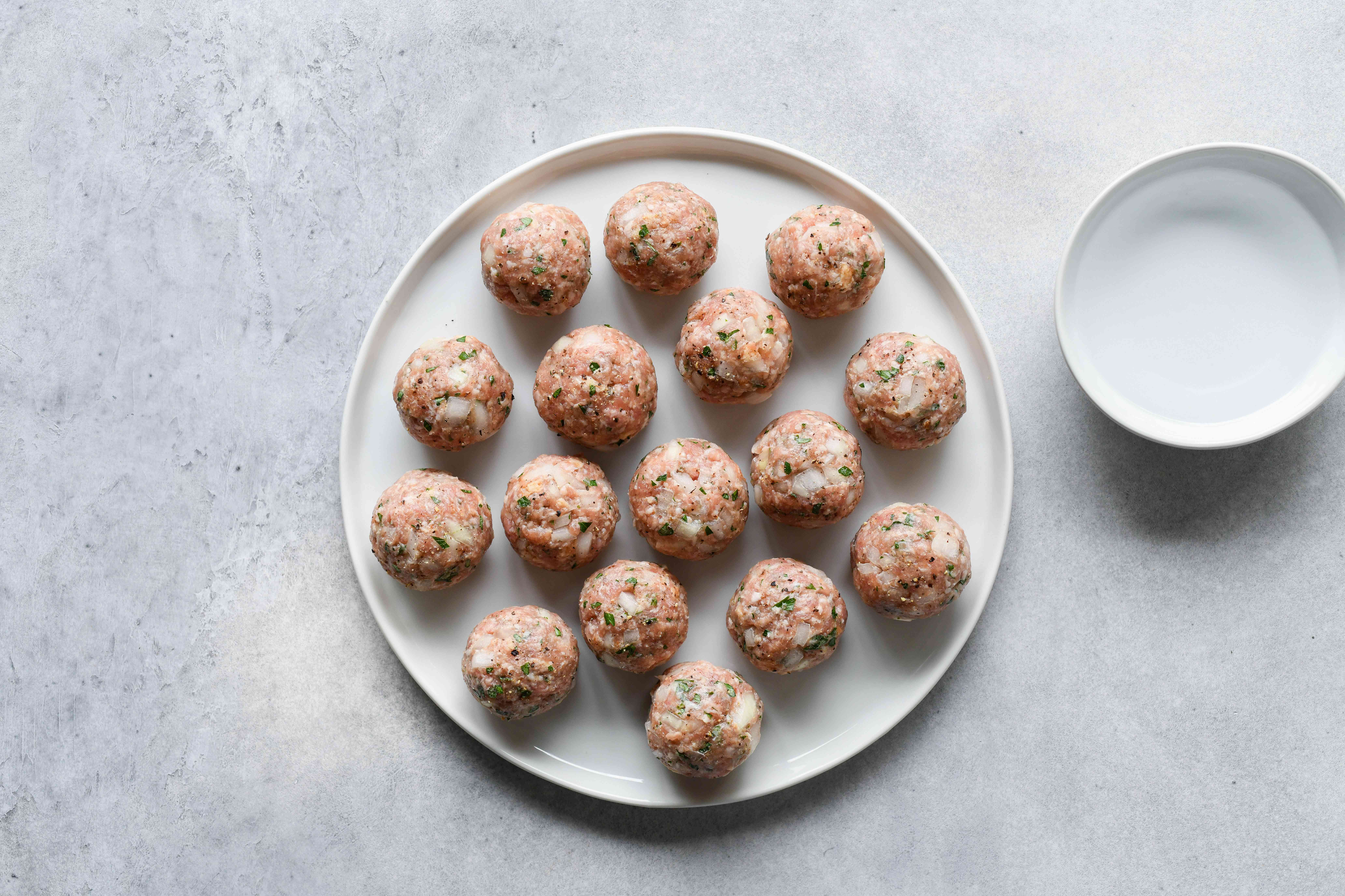 pork and onion meatballs rolled into balls on a plate