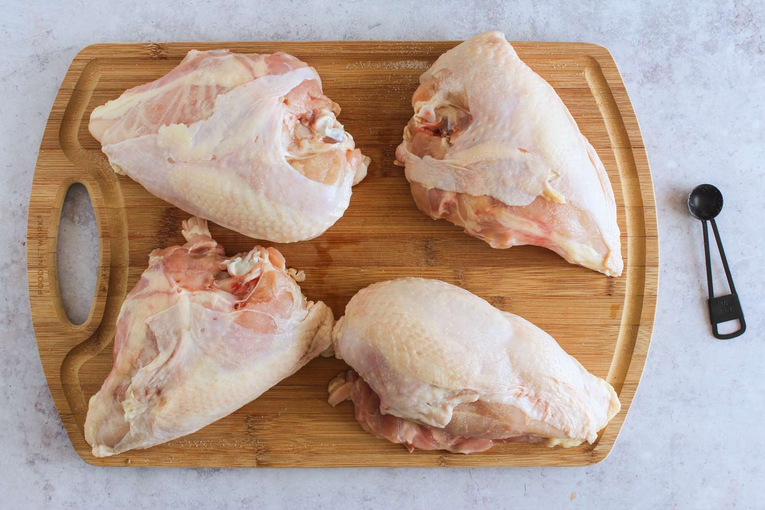 Chicken breasts sprinkled with salt on a wooden cutting board