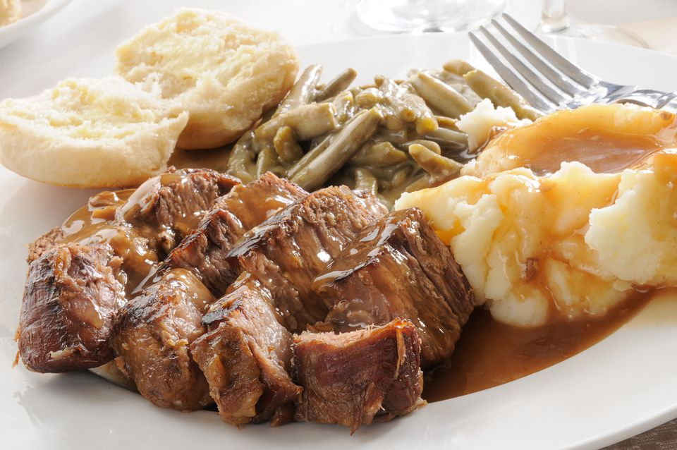 Pot roast with mashed potatoes, green beans, and roll on a plate