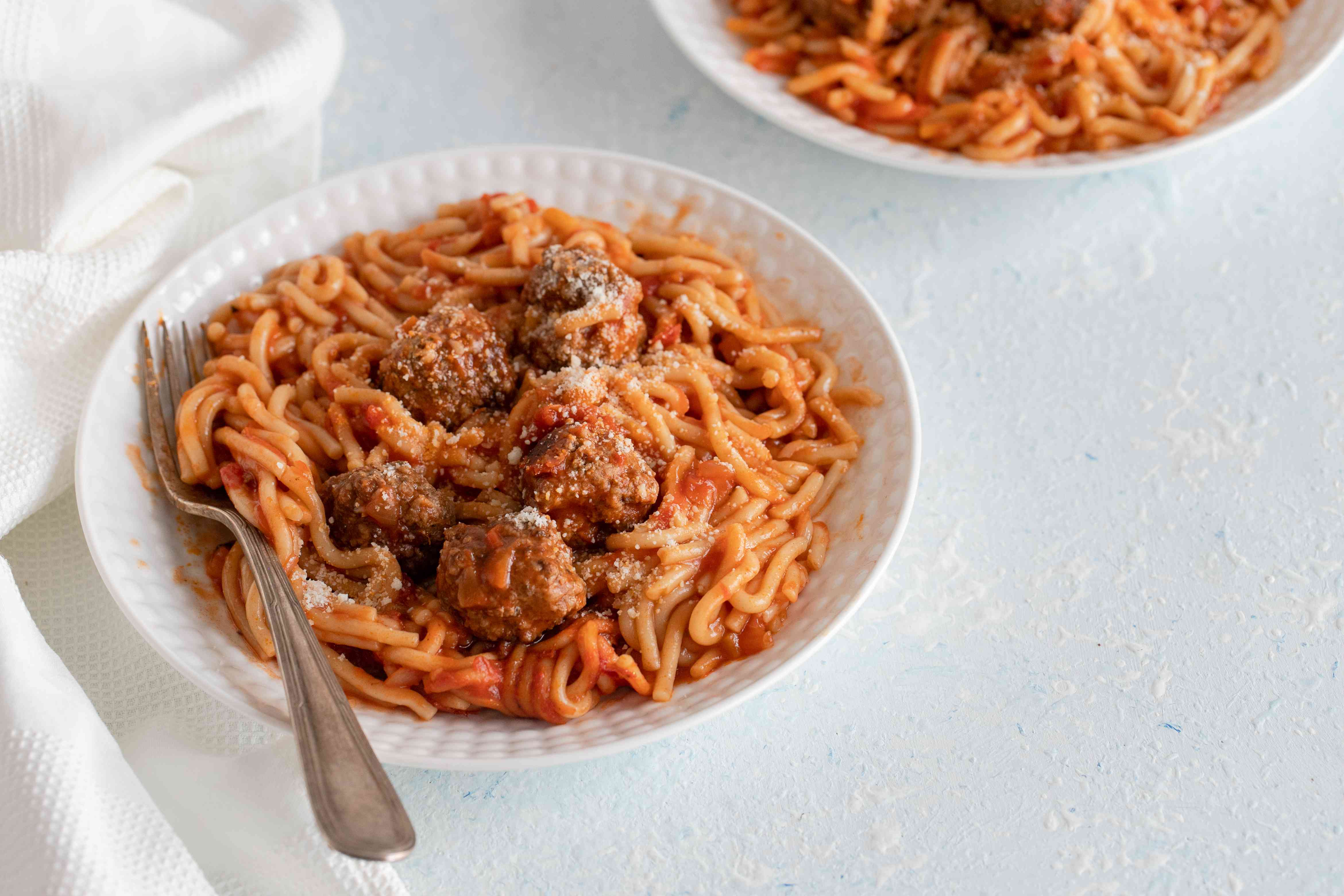 Spaghetti and meatballs topped with cheese