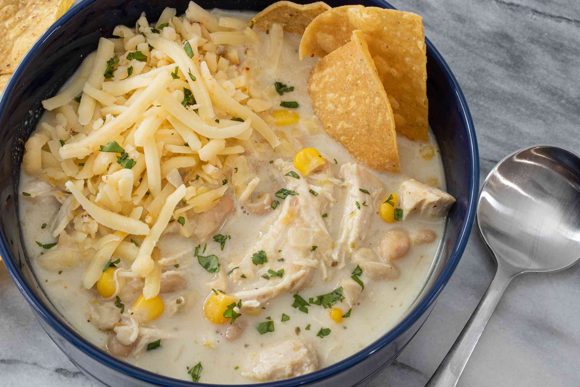 bowl of white chicken chili with extra cheese, cilantro, and tortilla chips