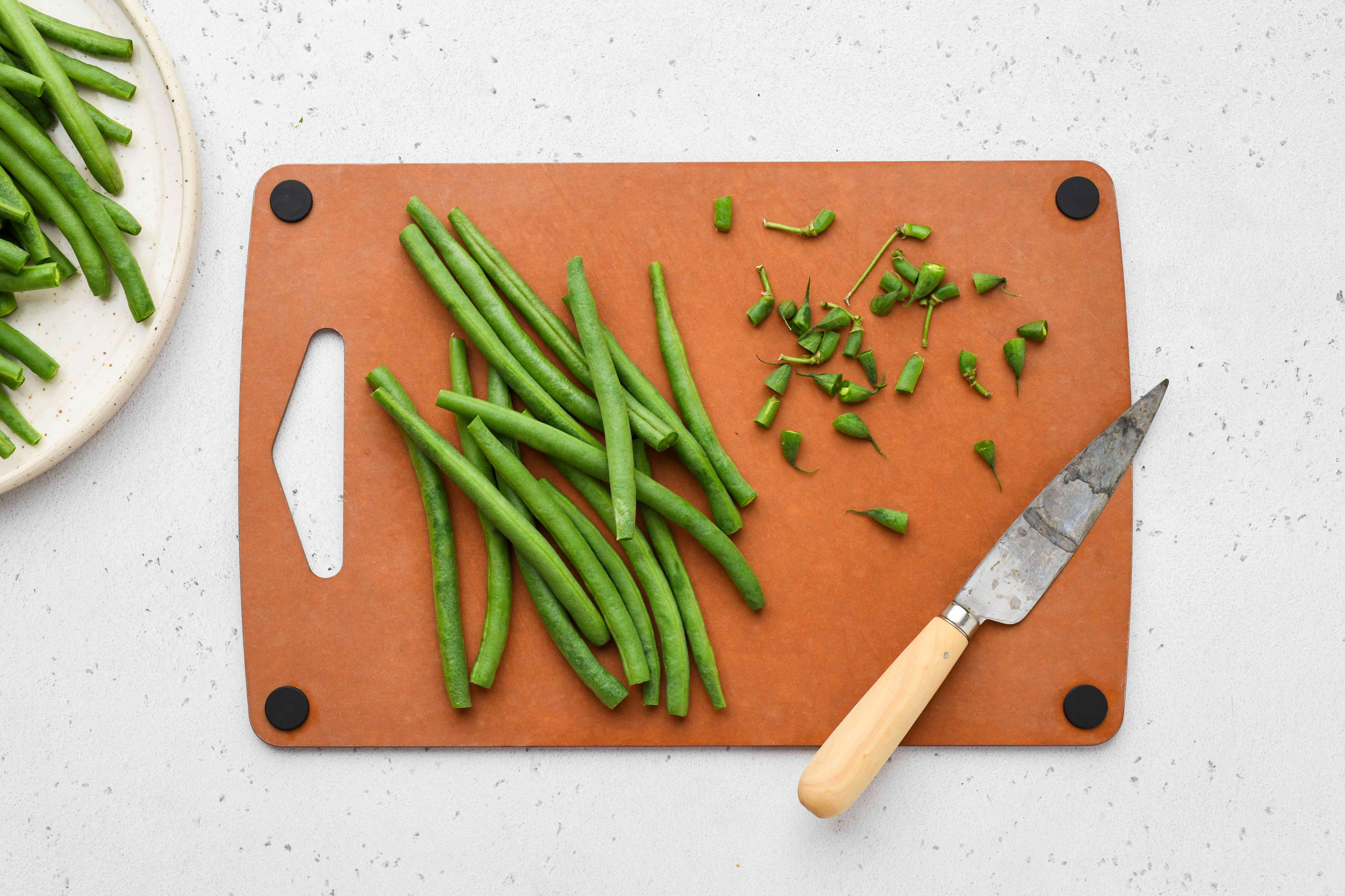 Trim the ends of the green beans on a cutting board