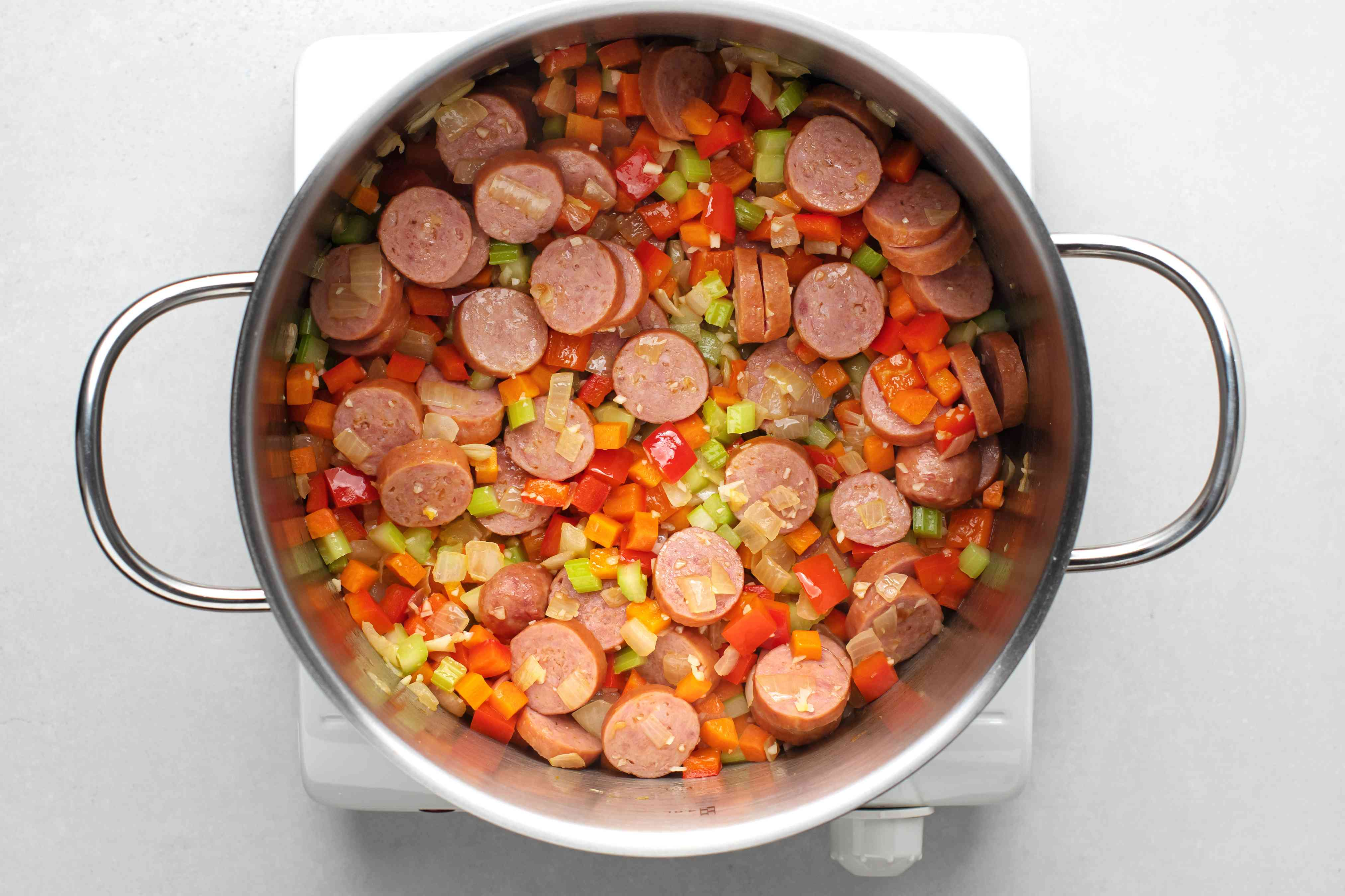 onions, carrots, bell pepper, celery, minced garlic, and sausage cooking in a pot