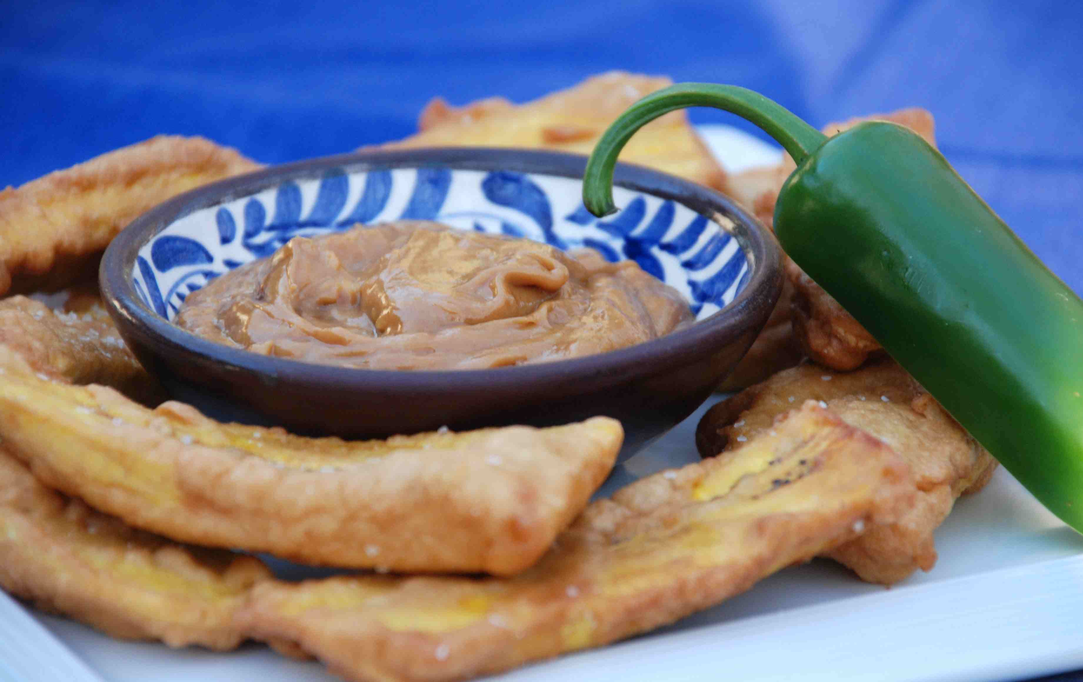 Fried plantains with a bowl of spicy peanut sauce
