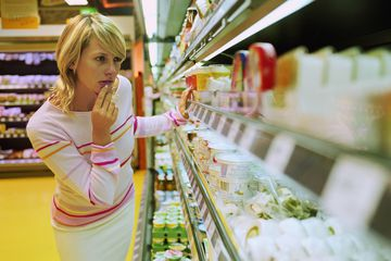 Young woman looking at dairy produce in supermarket