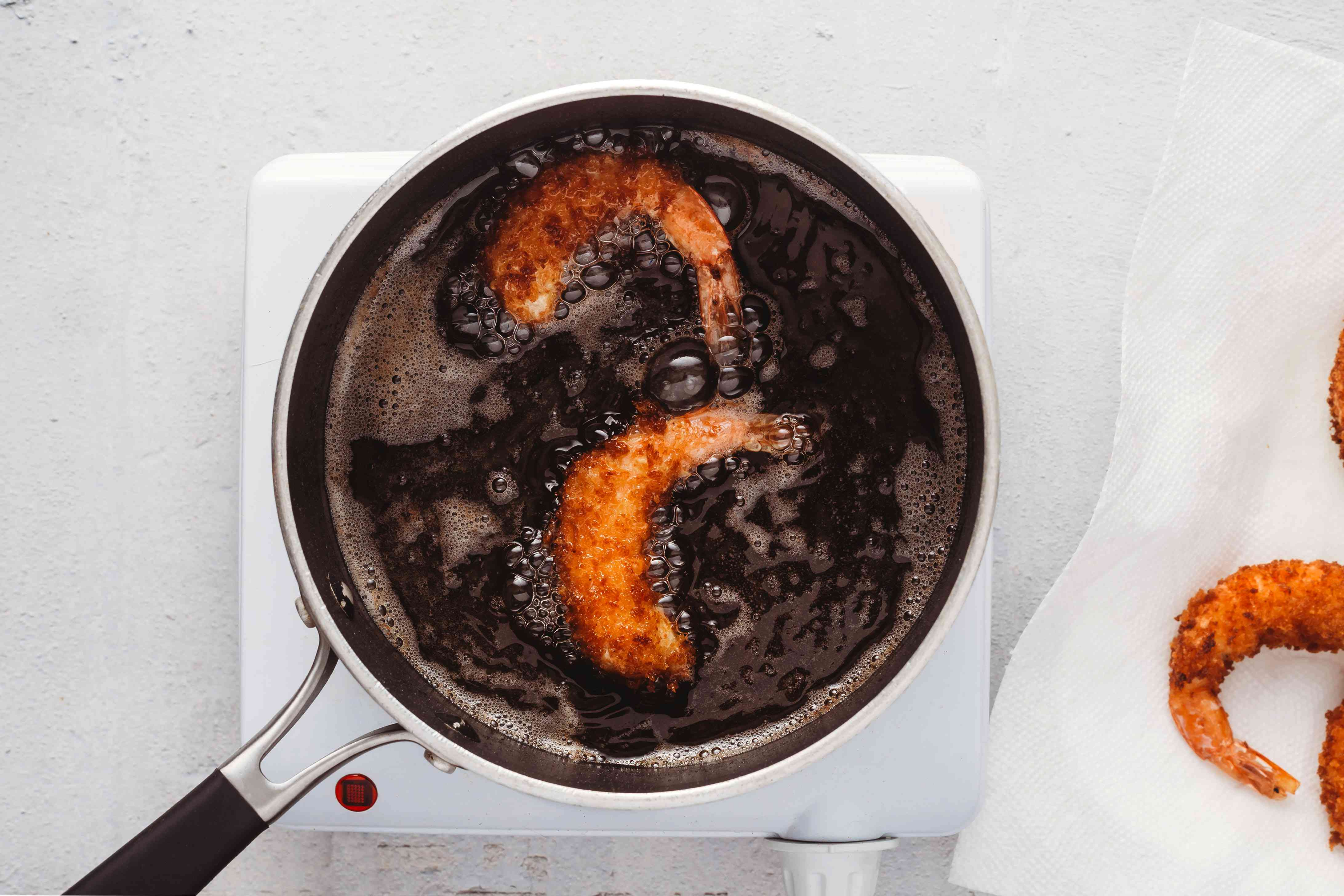 shrimp frying in a pot with oil