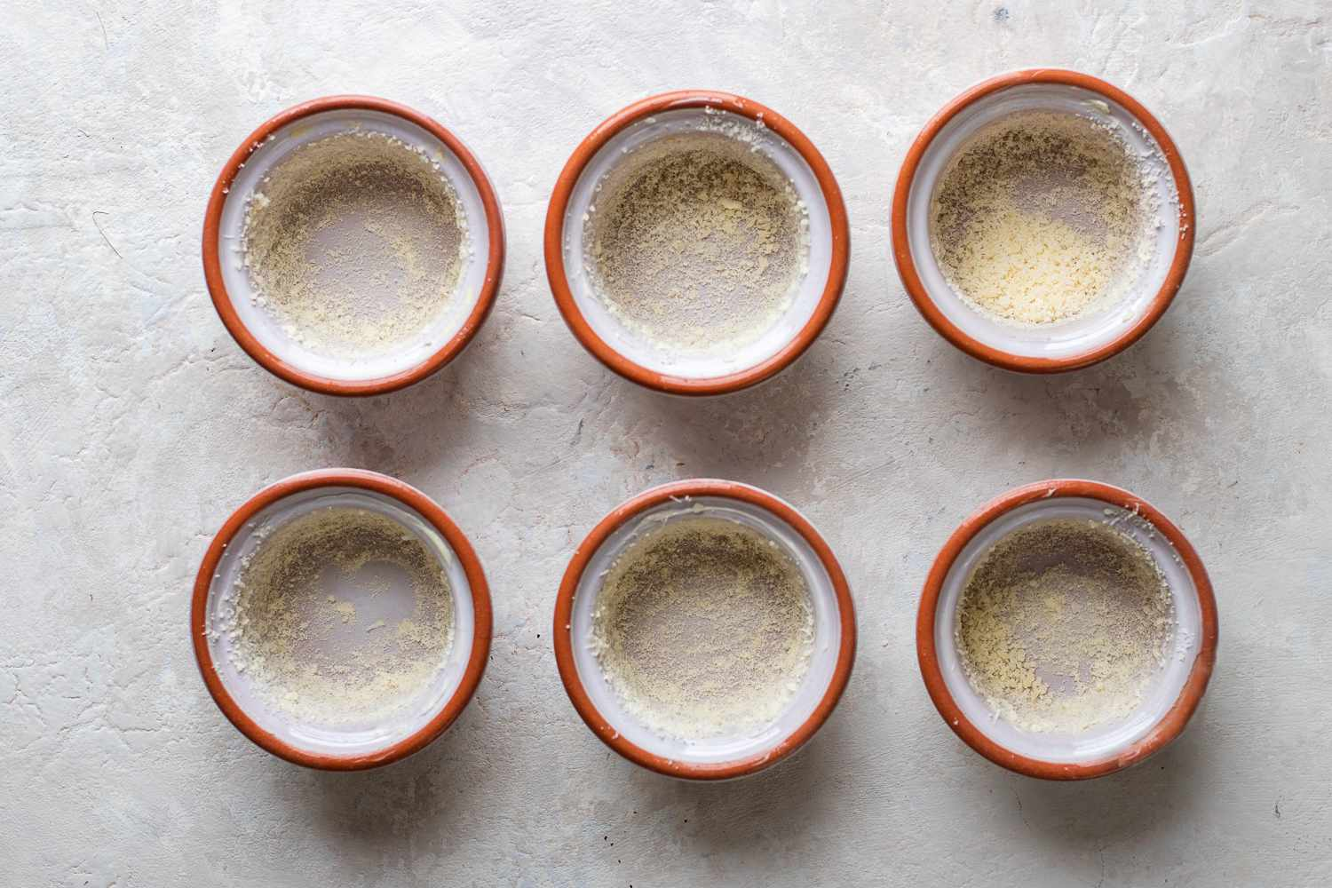 Sprinkle the buttered surface evenly with grated Parmesan cheese inside of a souffle ramekin