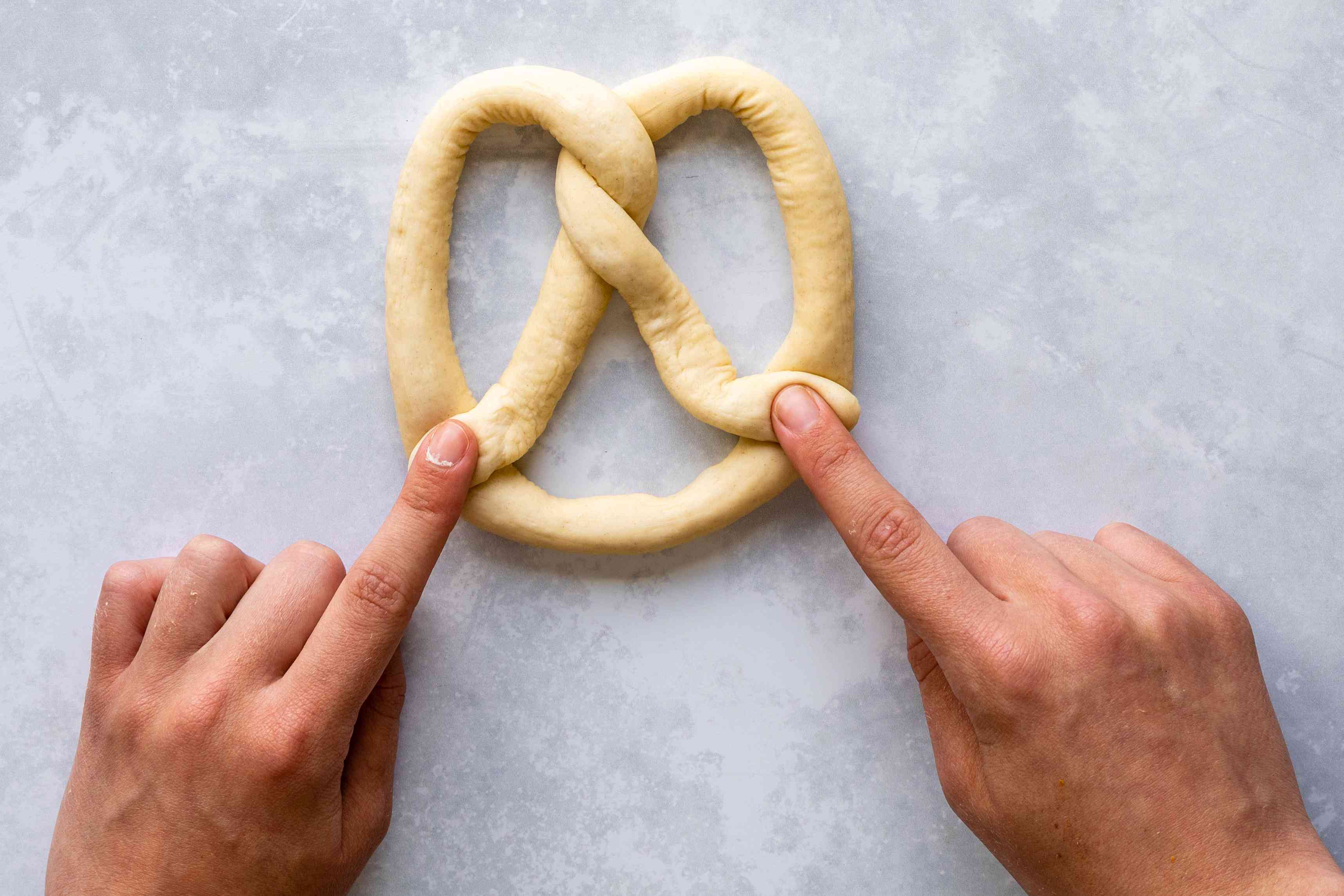 Pressing twisted dough ends to the bottom of the pretzel