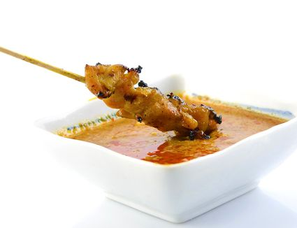 Chicken skewer dipped in traditional Thai peanut sauce in a white bowl