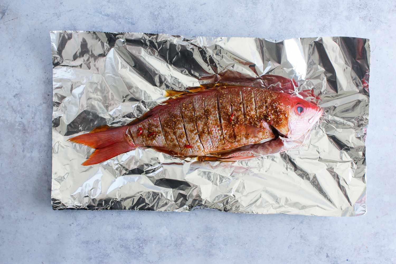 Scored whole fish and sauce on foil