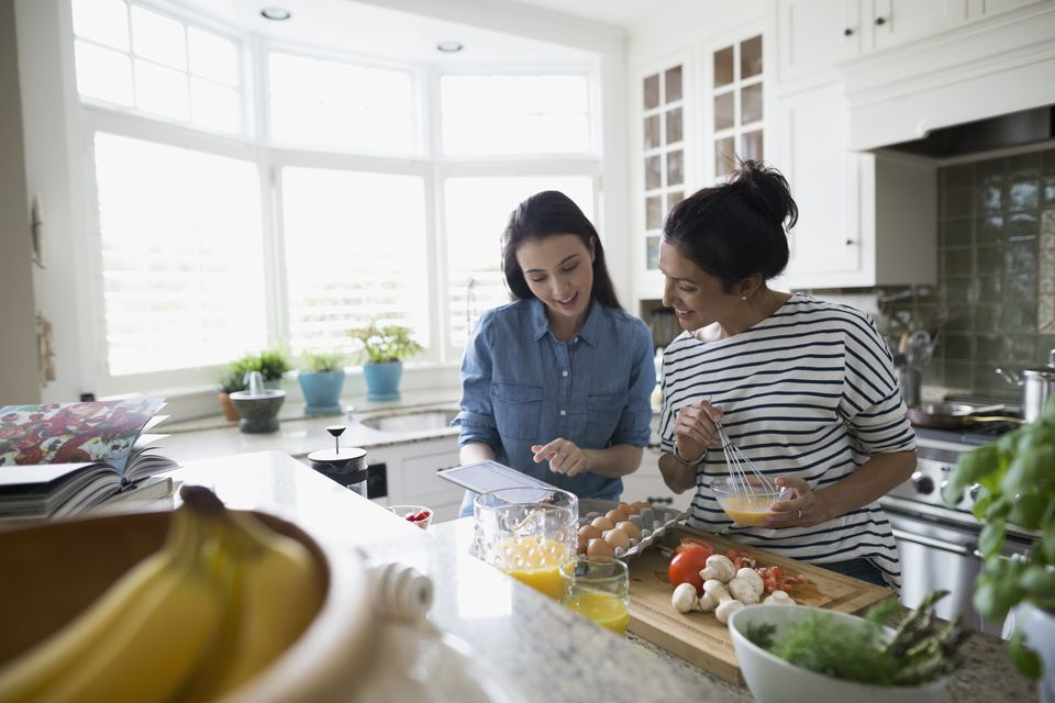 Mother and daughter cooking with recipe in kitchen