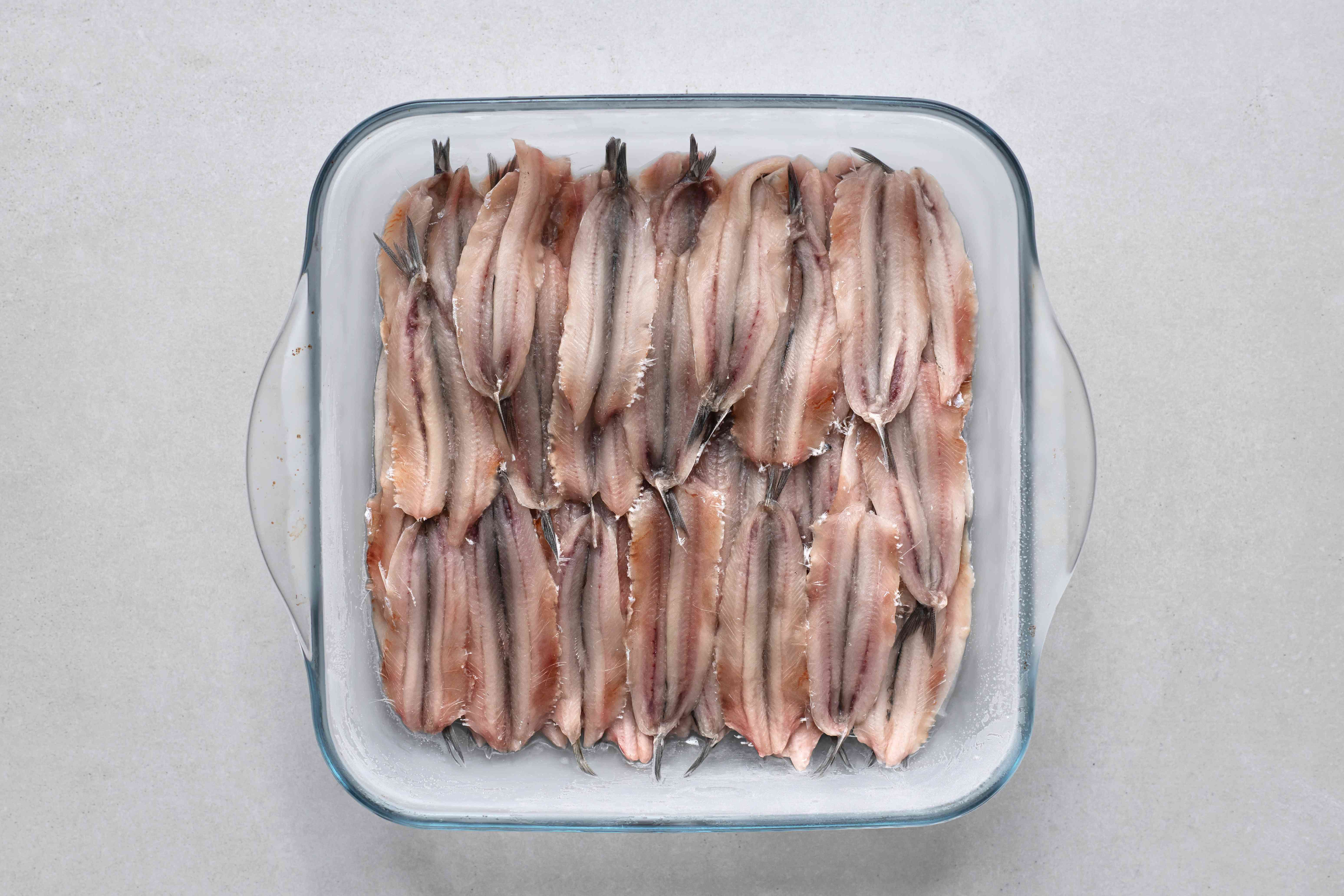 frozen anchovies in a glass baking dish