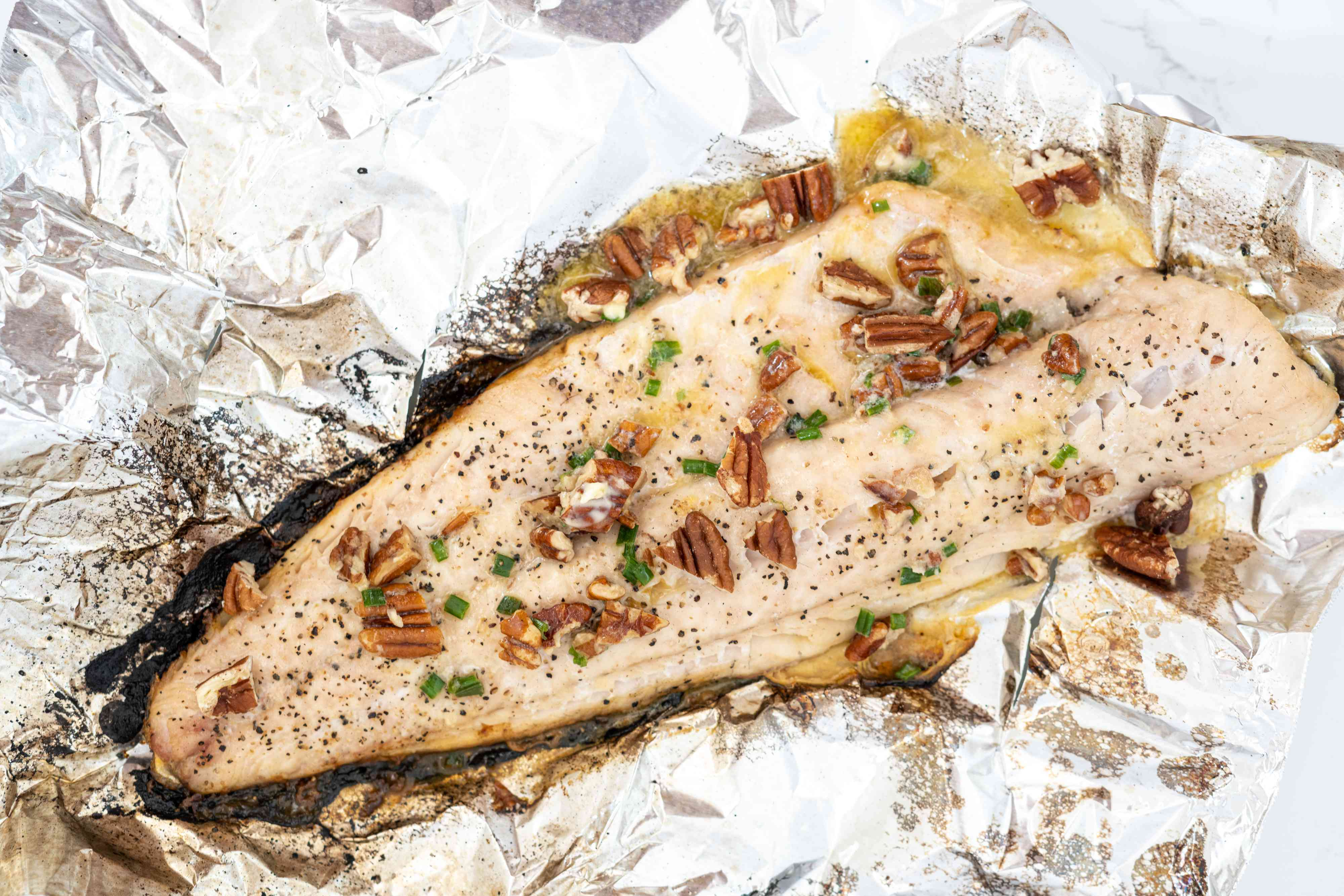 Grilled walleye with citrus butter, garnished with pecans