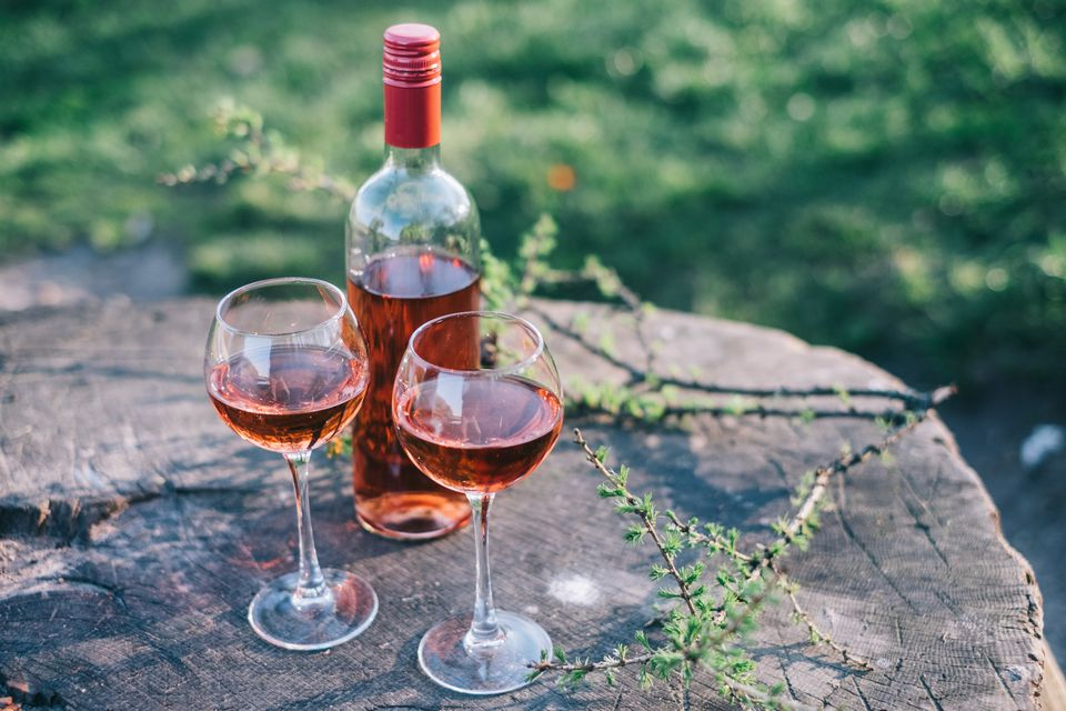 Rose Wine bottle and two half-filled glasses outdoors