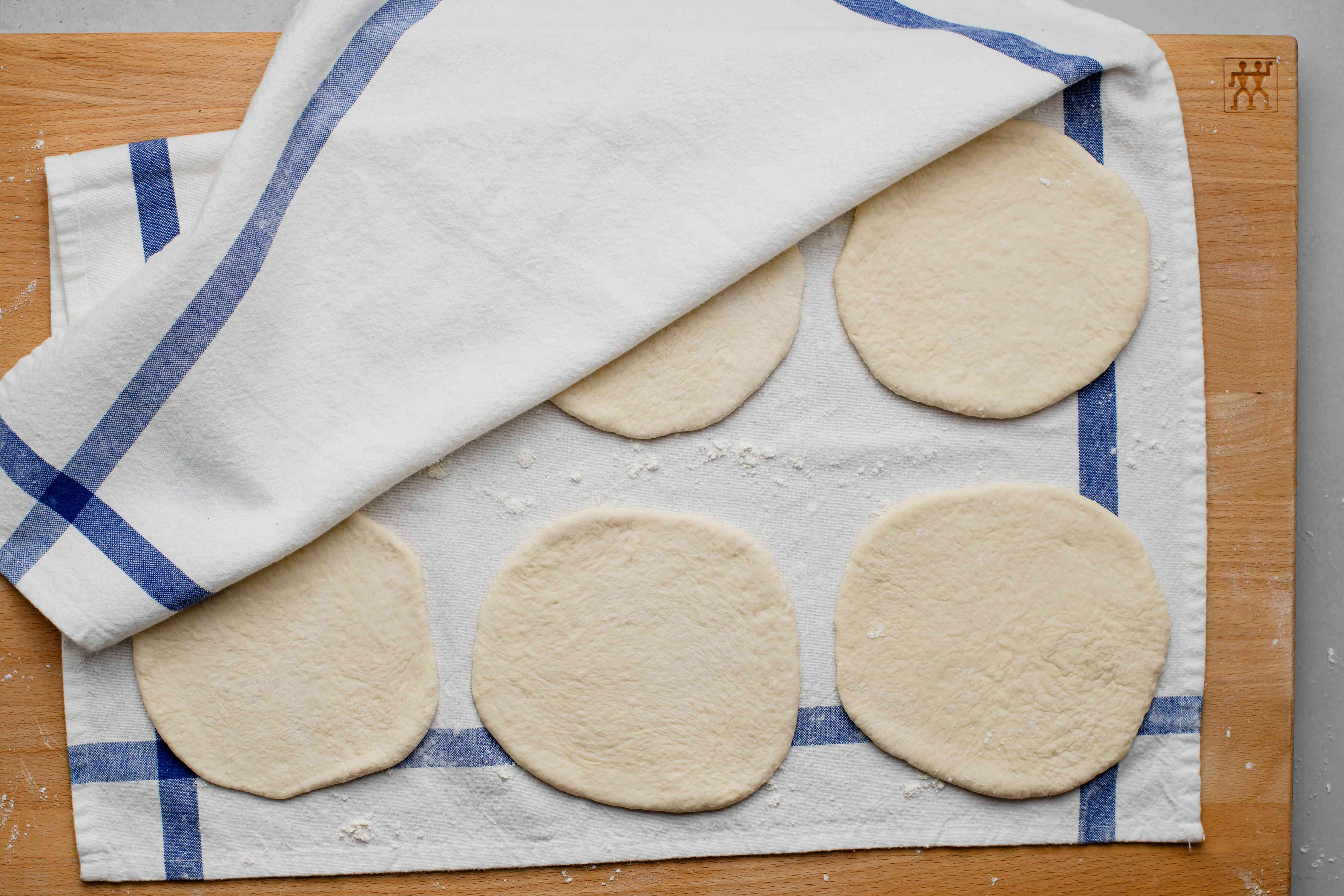 rolled out dough pieces between floured towels