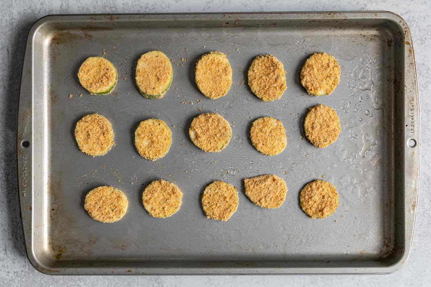 breaded zucchini pieces on a greased baking sheet