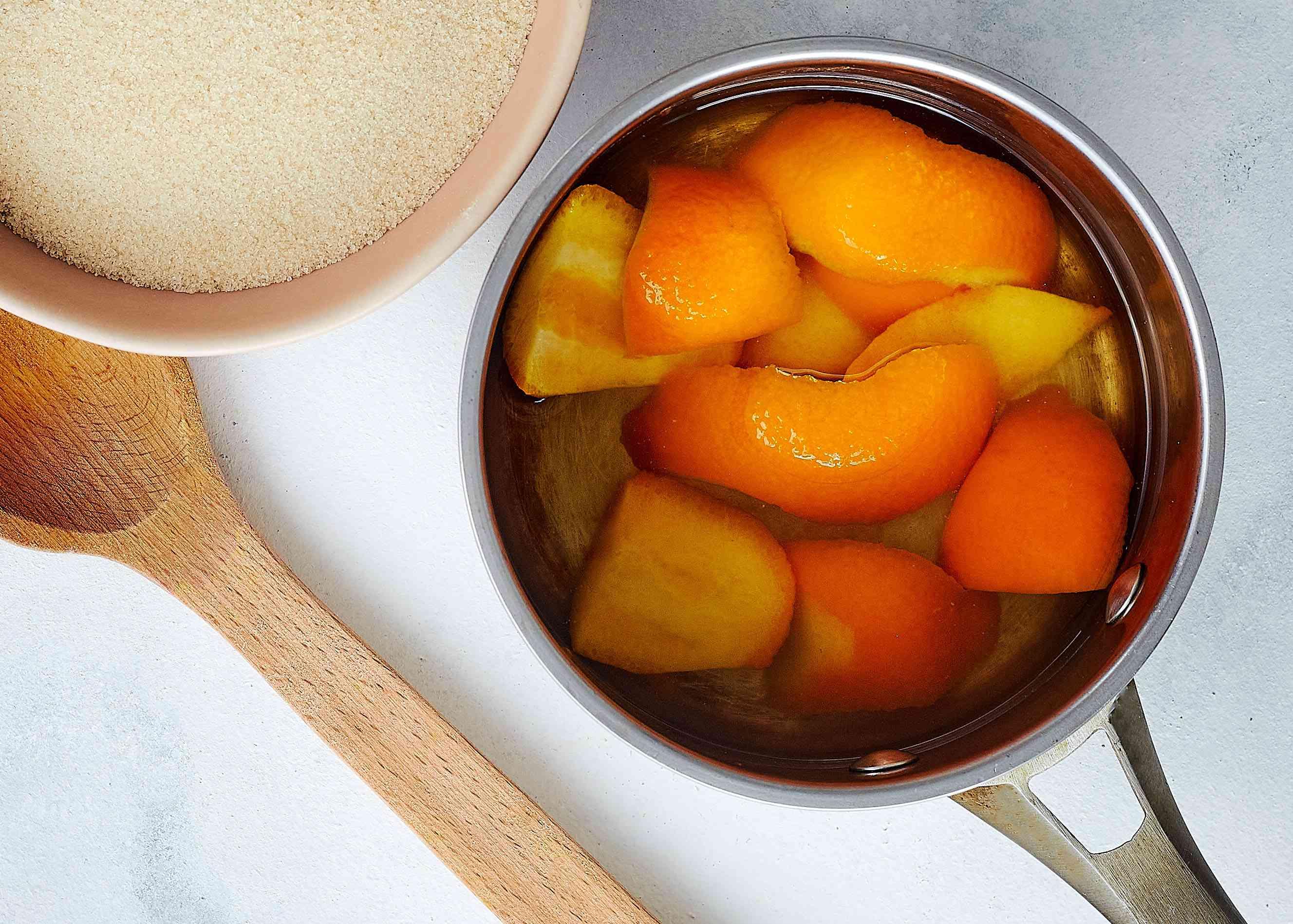 Water, sugar and orange peels in a pan