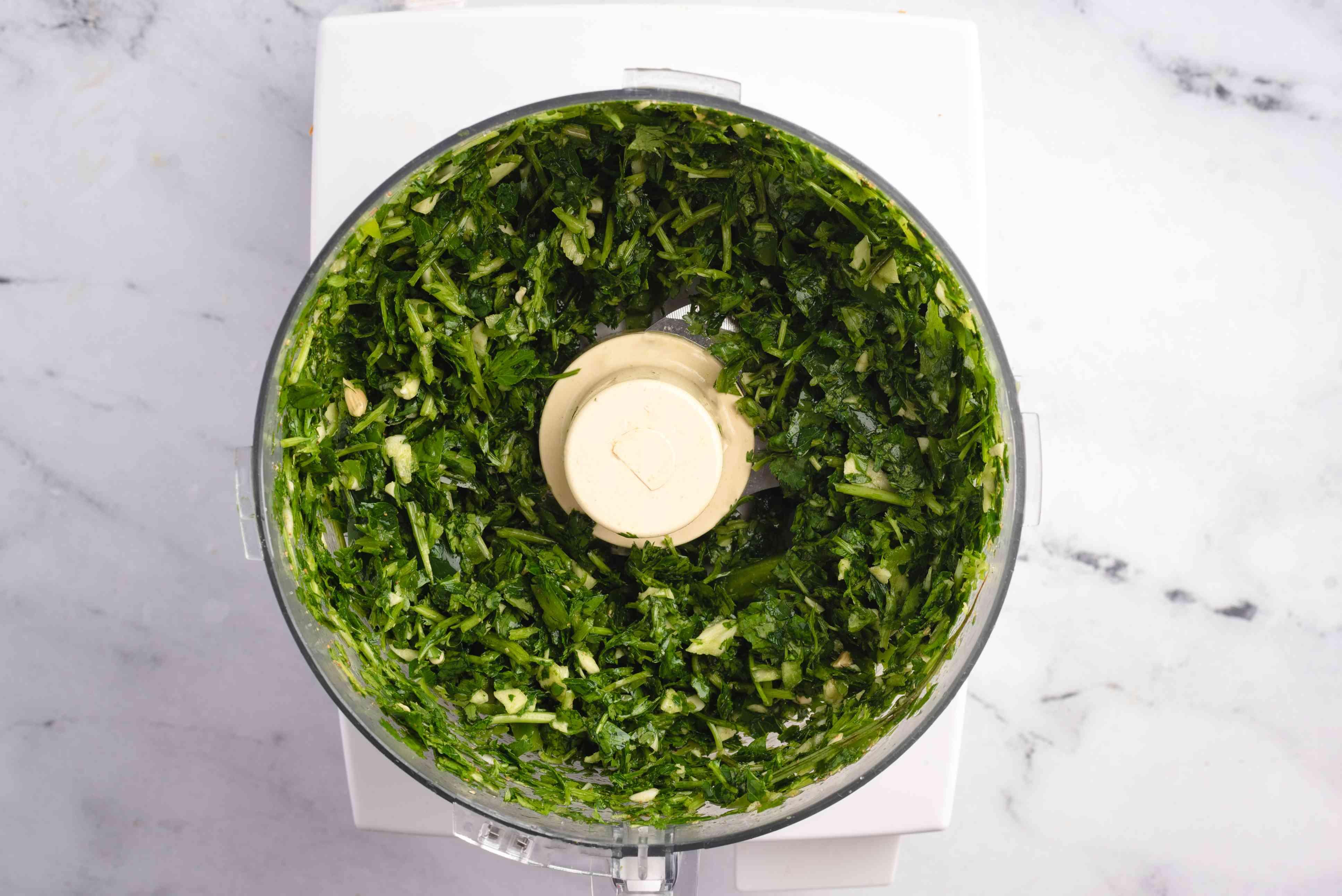 Garlic cloves, parsley, cilantro, lemon juice, salt, ground cumin, and ground coriander in a food processor