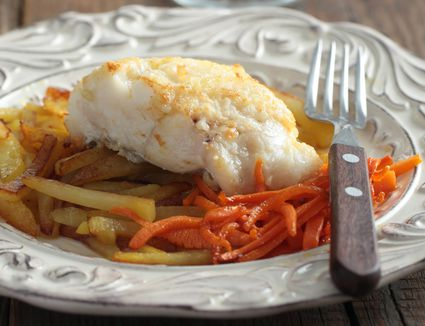 Halibut on a plate with roasted potatoes.