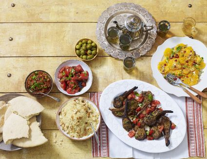 Moroccan dinner, including zahlouk (aubergine dip), kesra (bread), kesksou (couscous), lahma meshwi (lamb), olives, mint tea, salade doranges a la marocaine